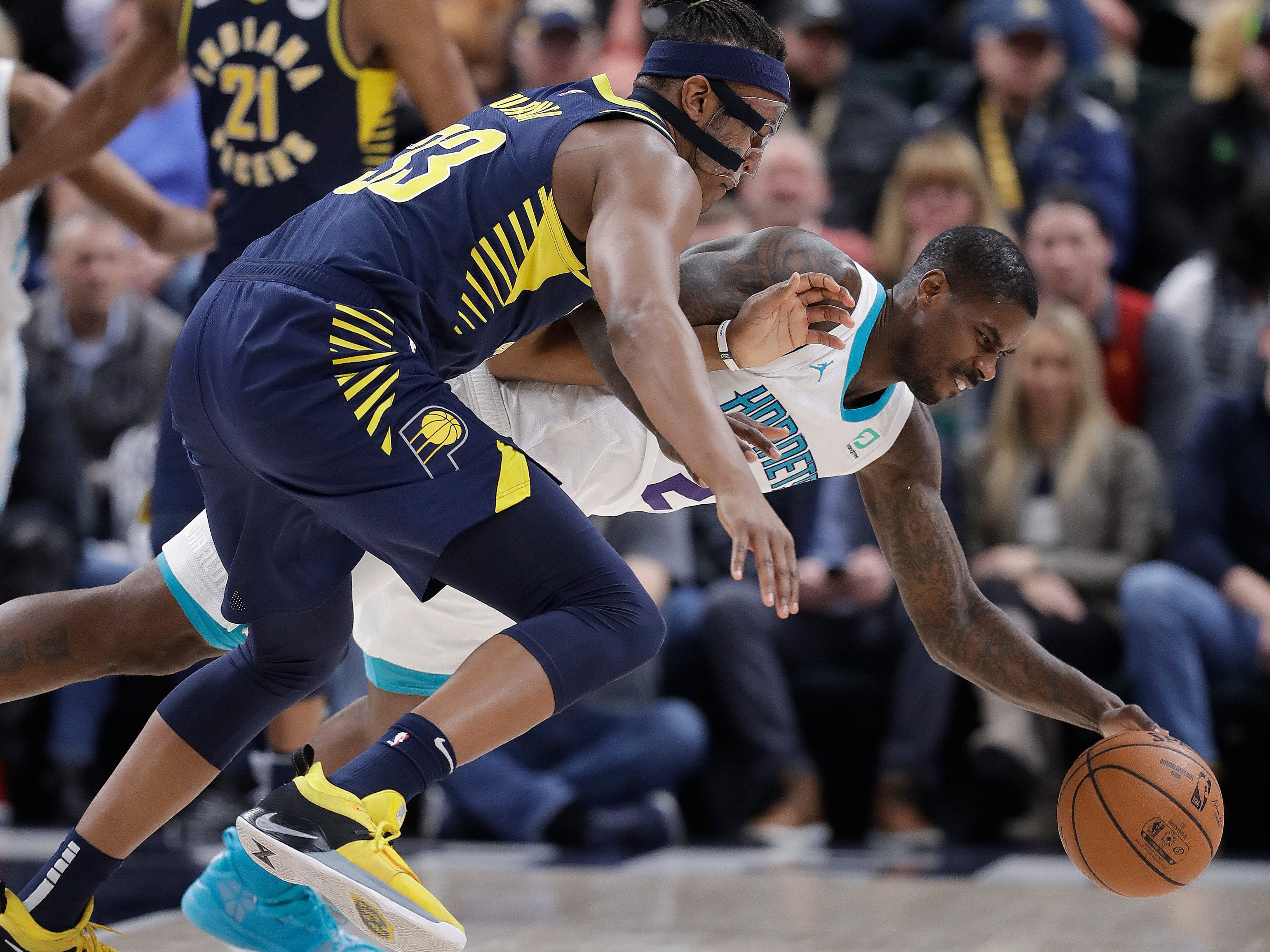 Indiana Pacers' Myles Turner, left, and Charlotte Hornets' Marvin Williams, right, battle for a loose ball during the first half of an NBA basketball game, Monday, Feb. 11, 2019, in Indianapolis.