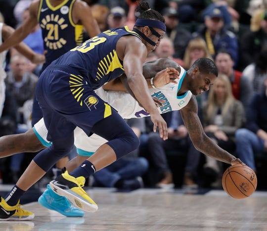 Indiana Pacers' Myles Turner, left, and Charlotte Hornets' Marvin Williams, right, battle for a loose ball.