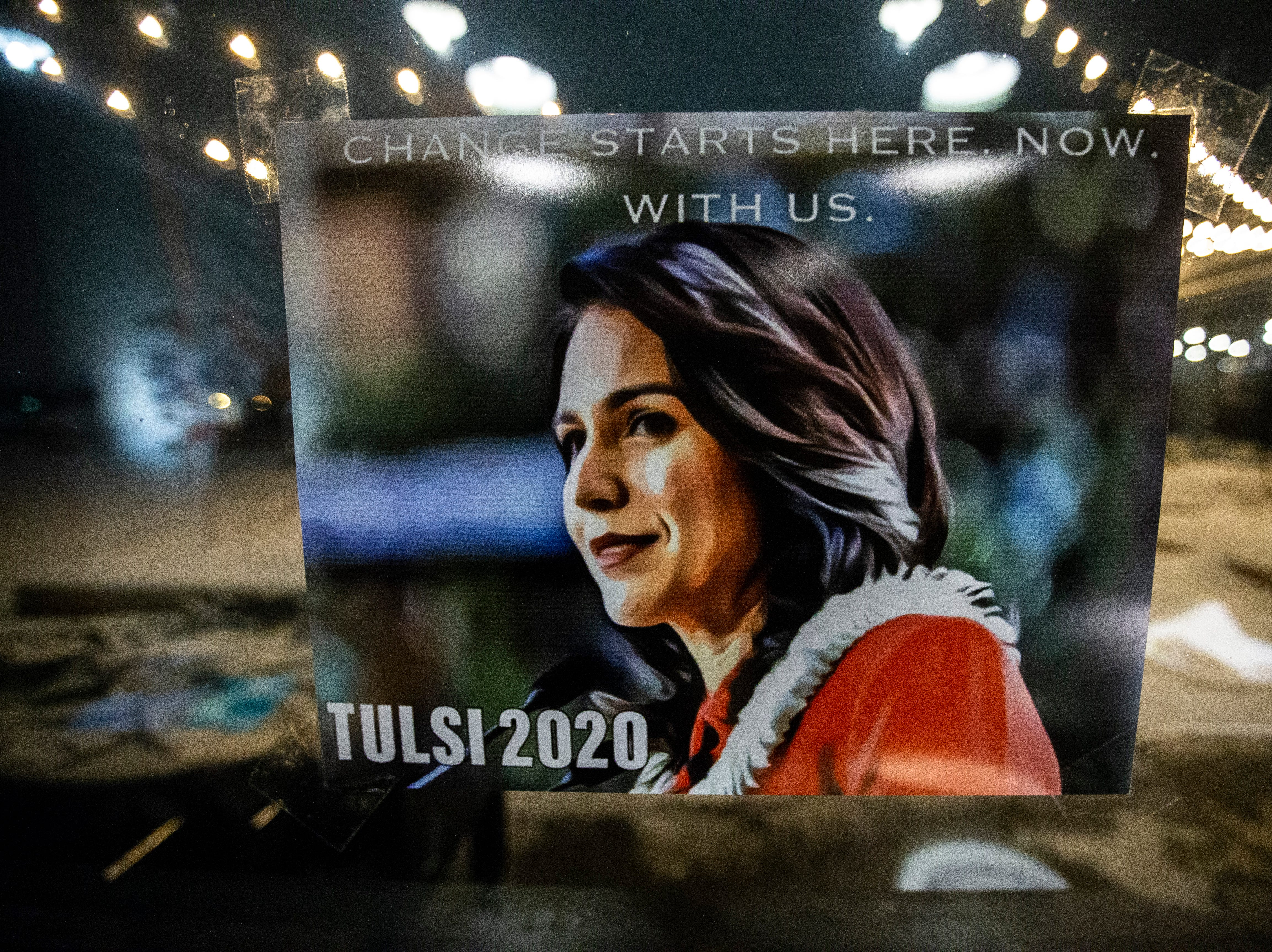 A sign hangs on a window as snow falls outside during an event U.S. Rep. Tulsi Gabbard, D-Hawaii, on her first trip to Iowa since declaring her intent to run for president on Monday, Feb. 11, 2019 at Big Grove Brewery in Iowa City.