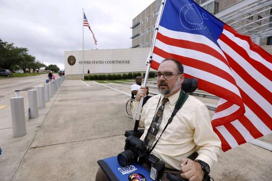 In this June 29, 2017 file photo, Scott Crawford, with the Mississippi Coalition for Citizens with Disabilities, waves his disability symbol American flag outside the federal courthouse in Jackson as he and other Medicaid recipients, social service activists and supporters stage a protest outside the offices of Sen. Roger Wicker, R-Miss. Crawford has filed a lawsuit against Hinds County charging county buildings are not ADA compliant.