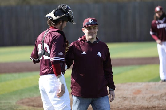 FHU baseball player Slater Springman walks off the field after throwing the opening pitch before the Lions' home opener Friday.
