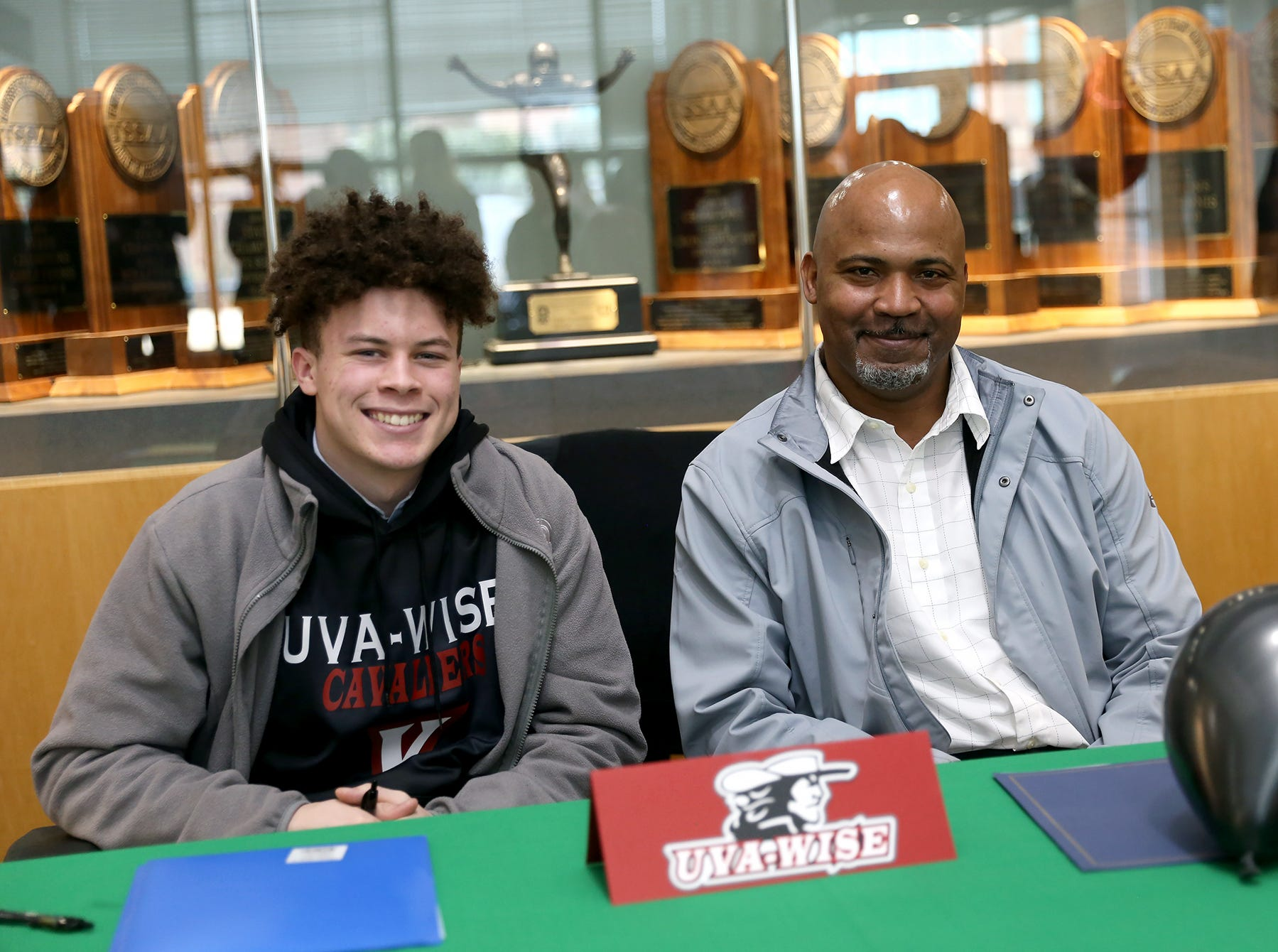 Webb senior running back, wide receiver and defensive back Roderick Lewis signed with University of Virginia's College at Wise, February 6. Pictured is Lewis with his father, Roderick Lewis, in Webb's Lee Athletic Center.