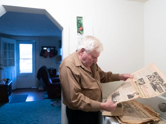 Harold Buckner looks at old newspaper stories on the killing of John Constant at his home in Englewood, Tenn., on Tuesday, Feb. 12, 2019. In 1982, Buckner was charged with killing Constant, but the charges were dropped the following year.
