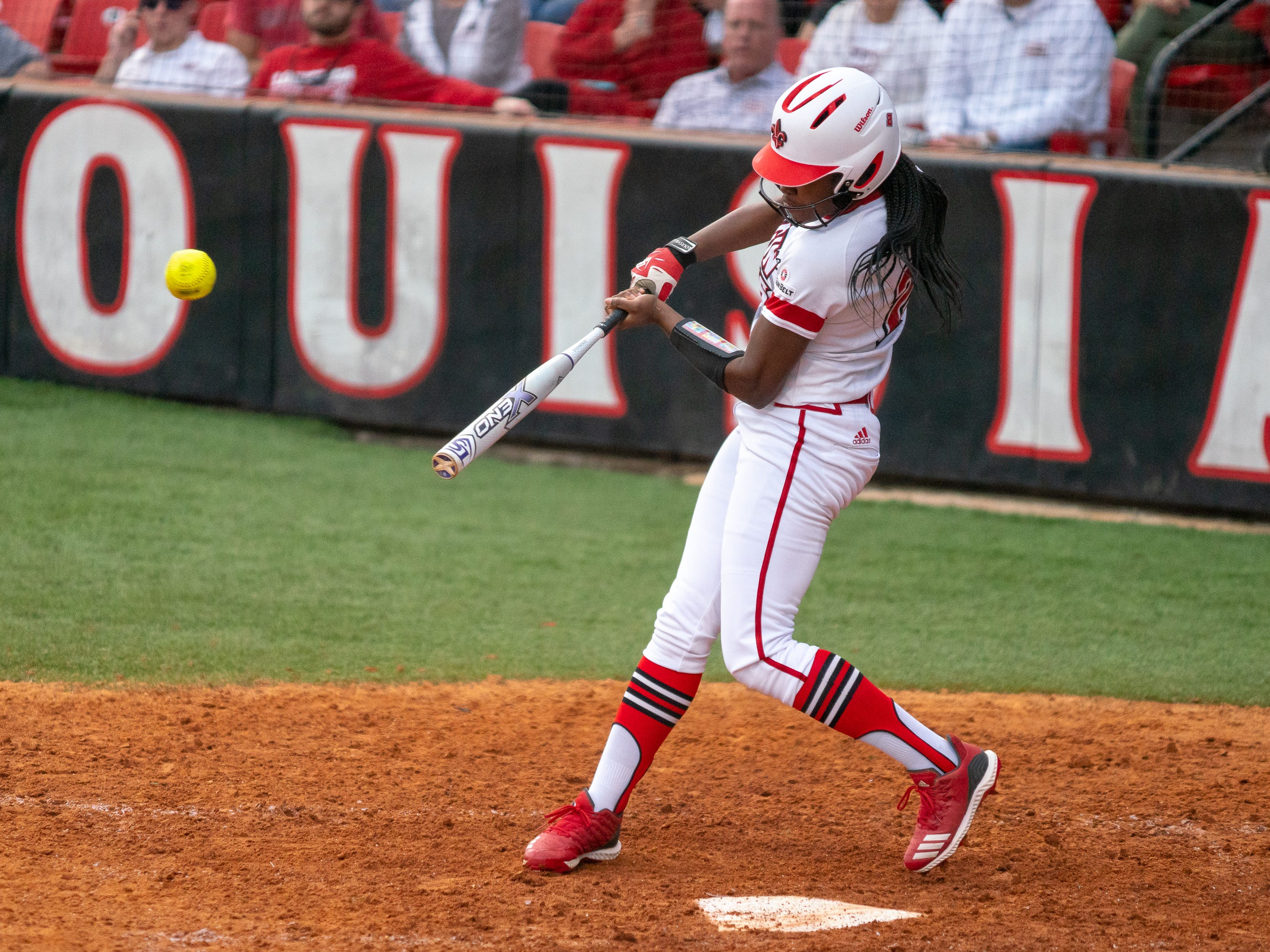 UL's Raina O'Neal hits the ball in the outfield as the Ragin' Cajuns play against the California Golden Bears at Lamson Park on February 11, 2019.