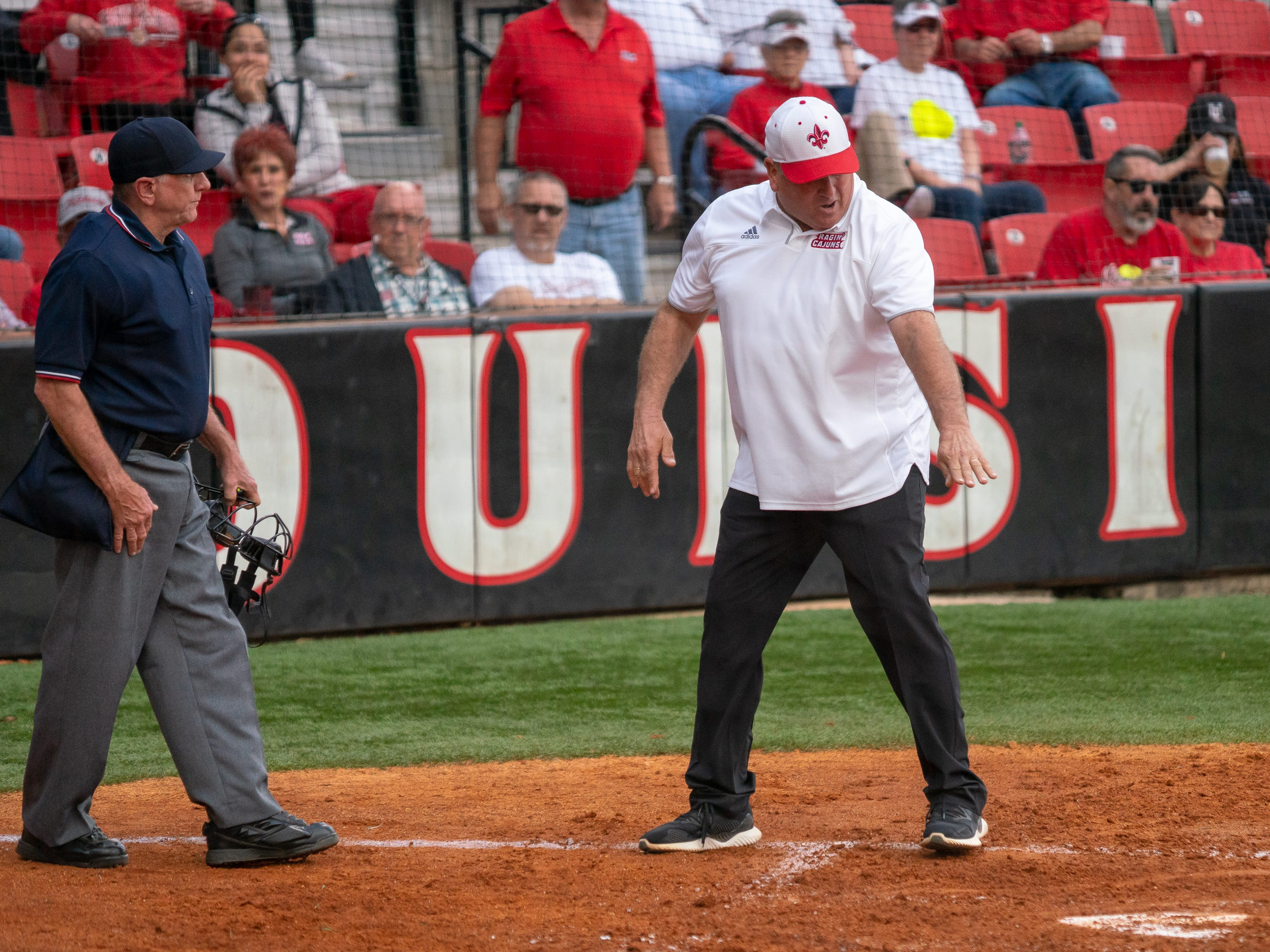 UL's head softball coach Gerry Glasco questions an official's call at home plate as the Ragin' Cajuns play against the California Golden Bears at Lamson Park on February 11, 2019.