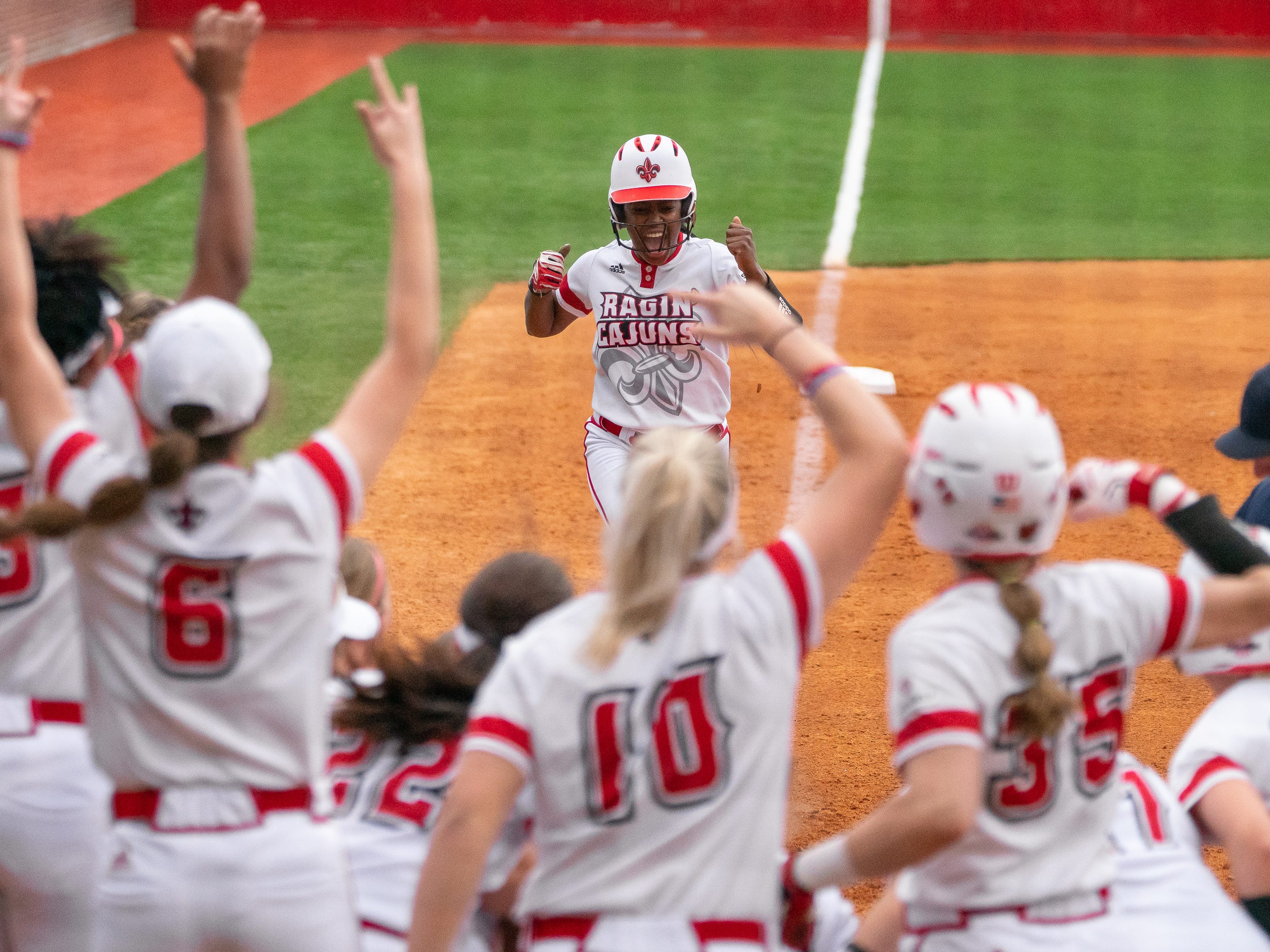 UL's Raina O'Neal excitedly runs to home plate after hitting a homerun as the Ragin' Cajuns play against the California Golden Bears at Lamson Park on February 11, 2019.