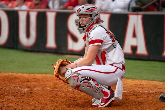 UL catcher Julie Rawls looks to her coaches in the dugout before a pitch during the Cajuns' Feb. 11 game against California at Lamson Park.