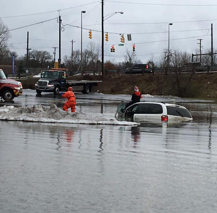 Firefighters rescue woman from flooded parking lot