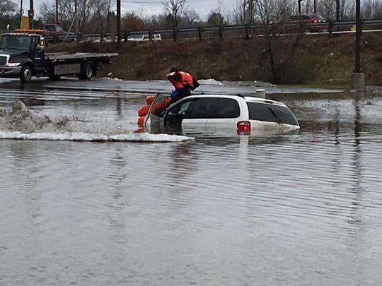 City firefighters rescue a woman in a parking lot at 1739 N. Memorial Drive when her SUV got submerged in standing water Tuesday afternoon. The woman was not injured.