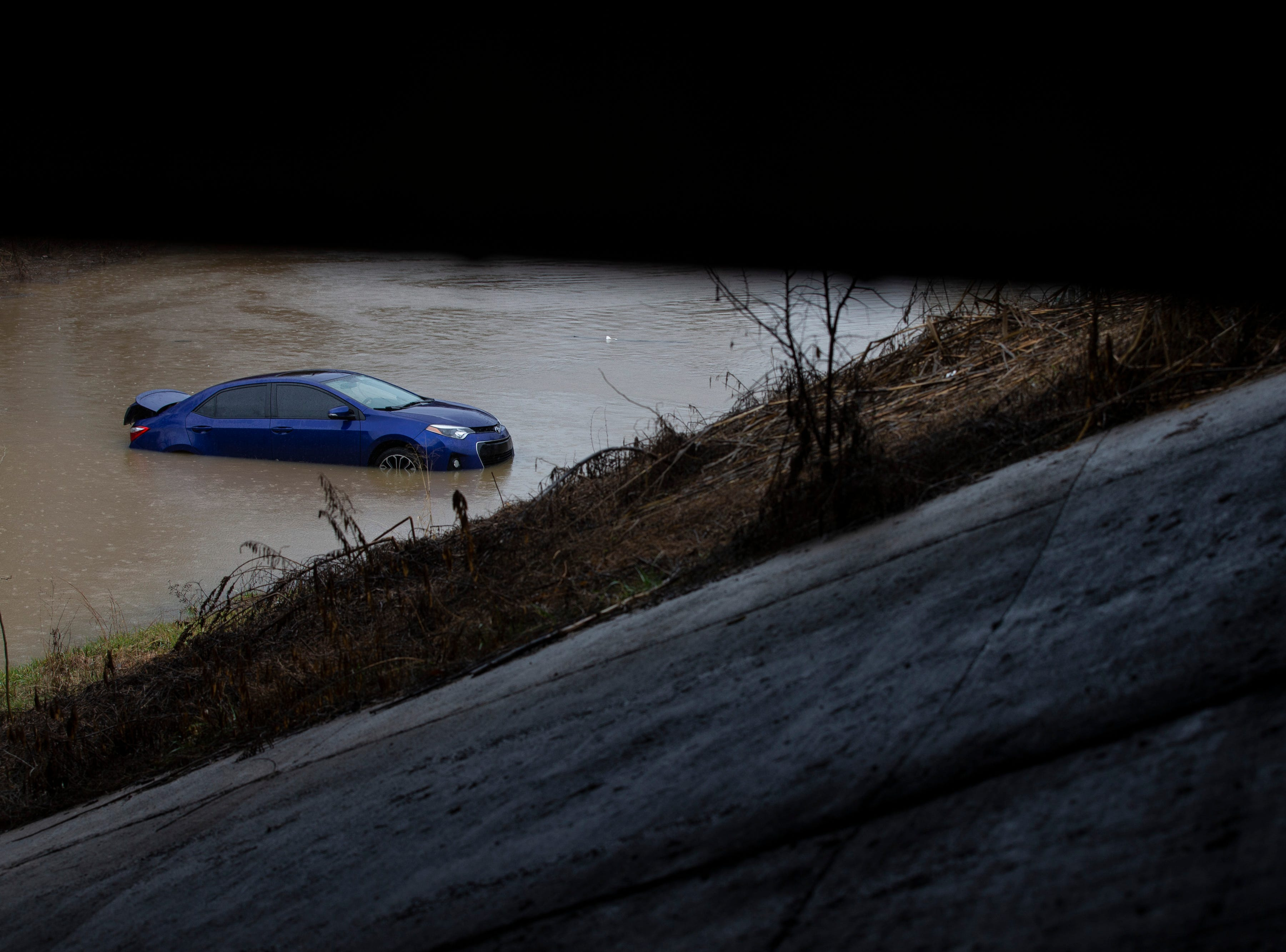 A car sits stuck in high water along Frankfort Avenue on Tuesday afternoon in Louisville. Feb. 12, 2019