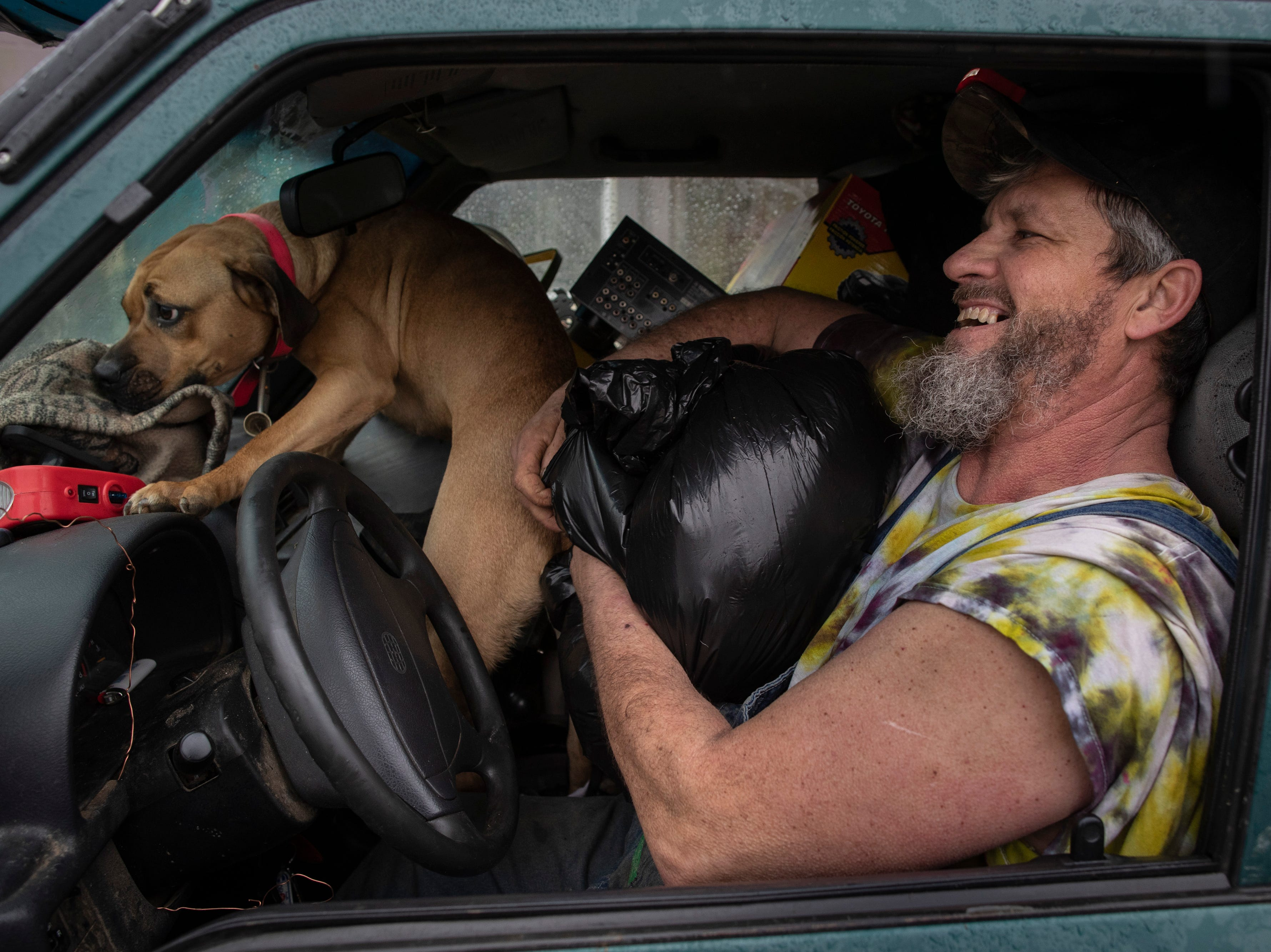 """Chip Jordan, right, has a laugh as he tries to fit all of his belongings into his vehicle with his dog Dixie Tuesday to escape the high waters along River Road. """"I had a compound fracture in my leg that kept me laid up six months while I dealth with this last year,"""" Jordan said. """"I still love it."""" Feb. 12, 2019"""