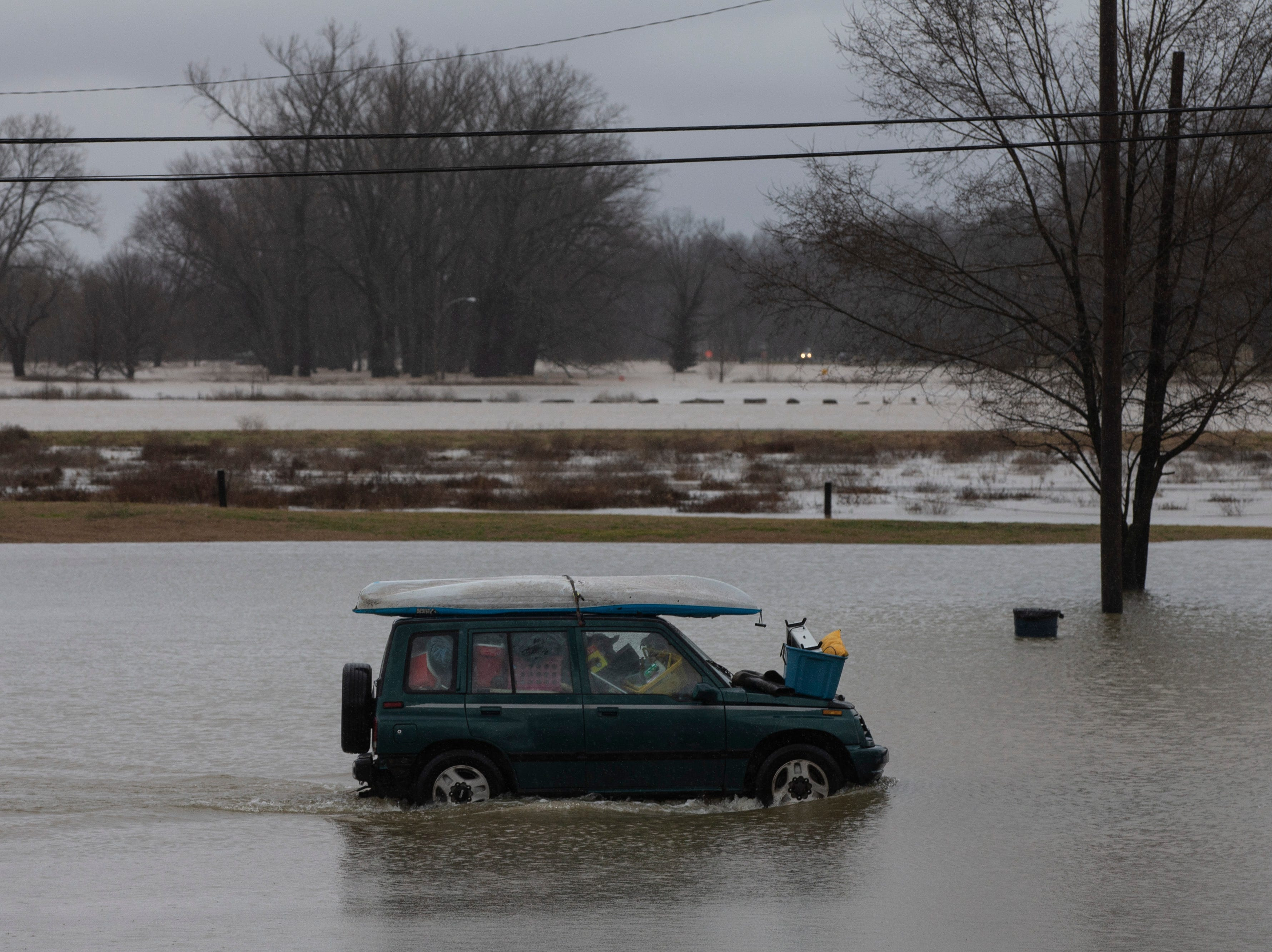 Chip Jordan drives with all of his belongings and his dog Dixie Tuesday to escape the high waters along River Road. Feb. 12, 2019