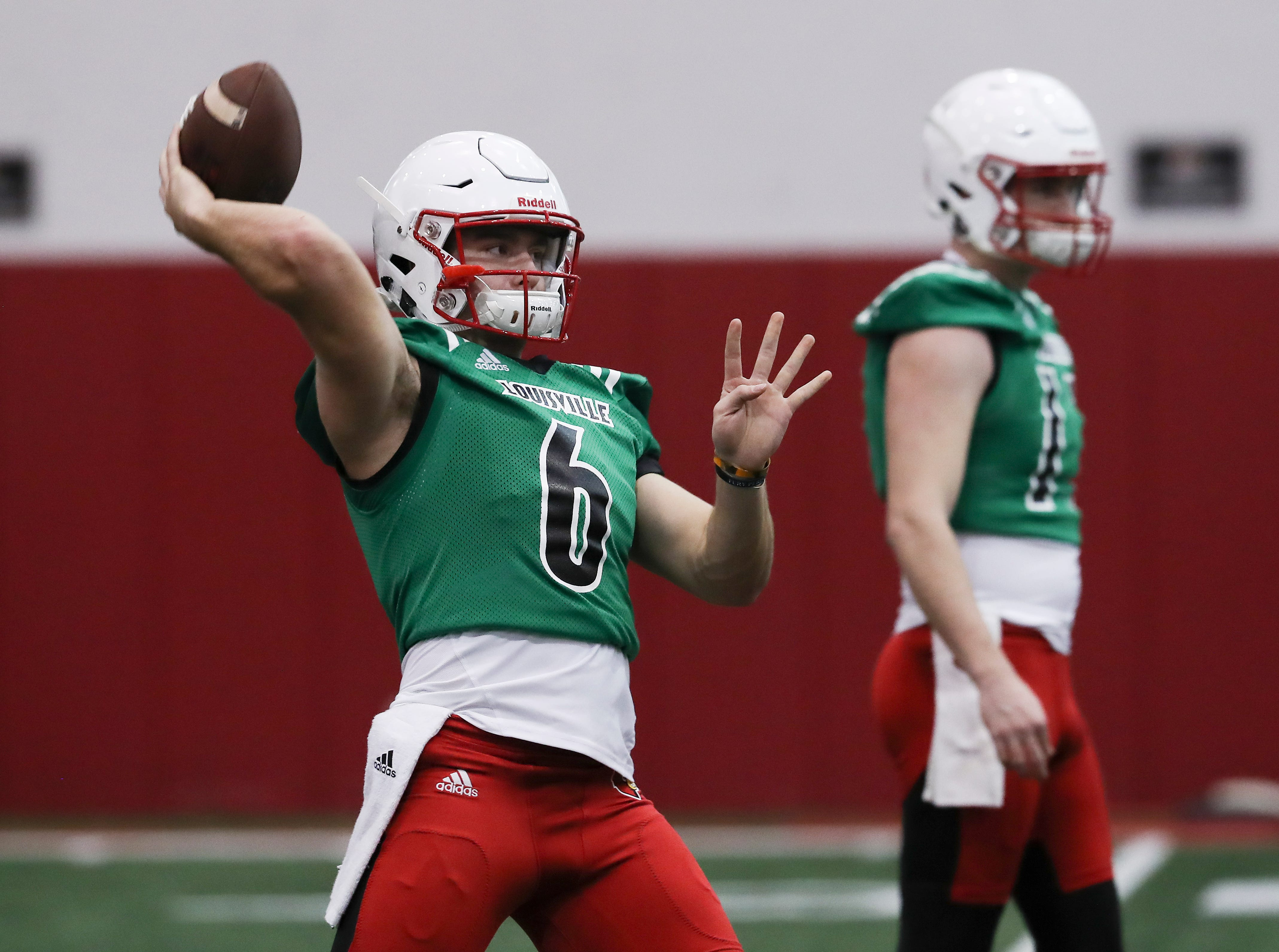 U of L QB's Evan Conley (6), left, and Drew Zaubi (17) perform pass drills during practice at the Trager Center.