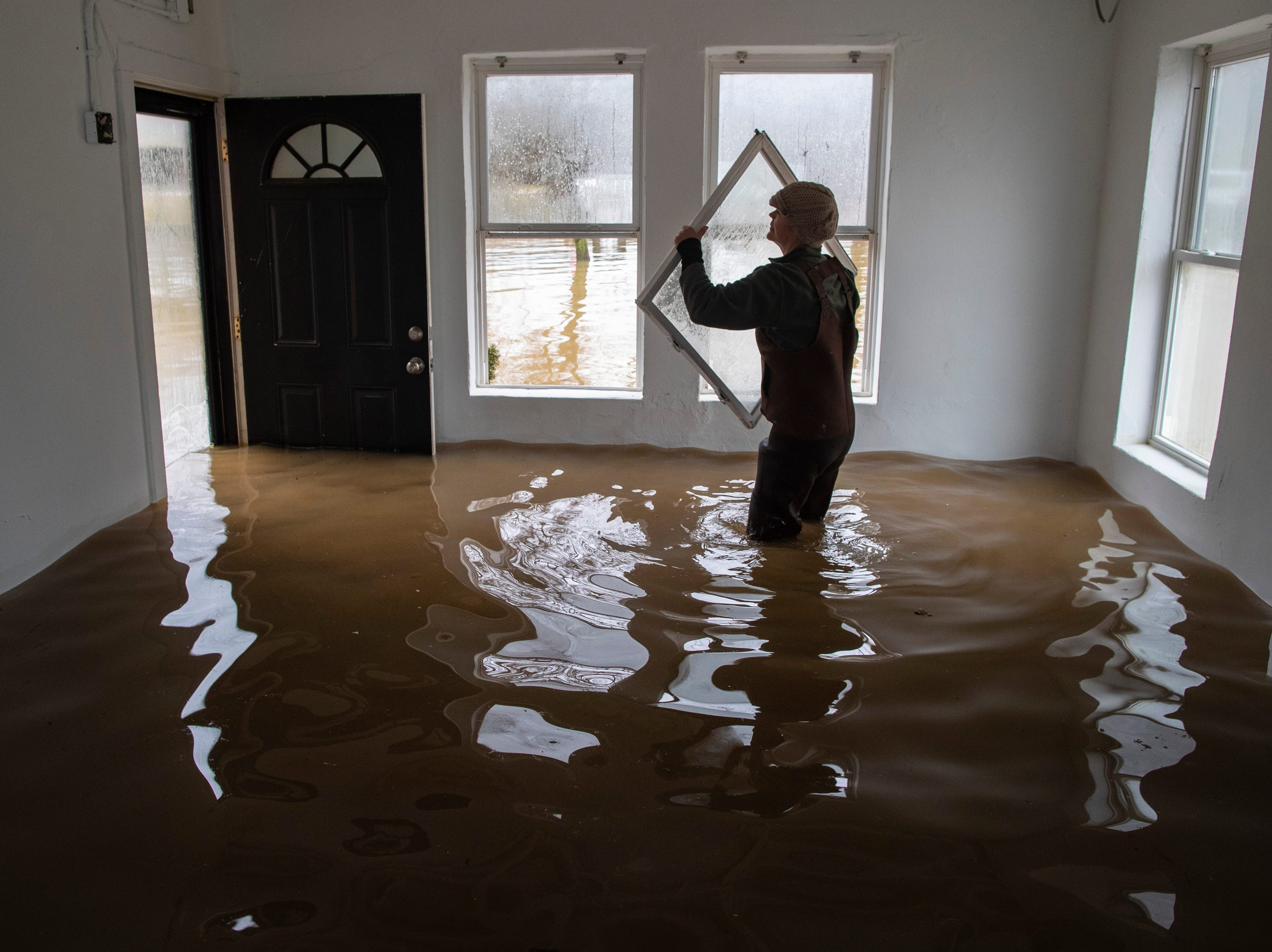 Angelyn Rudd pulls on her waders as she prepares to do some flood preparation at her home on River Road as high waters on the Ohio River rose Tuesday. Feb. 12, 2019