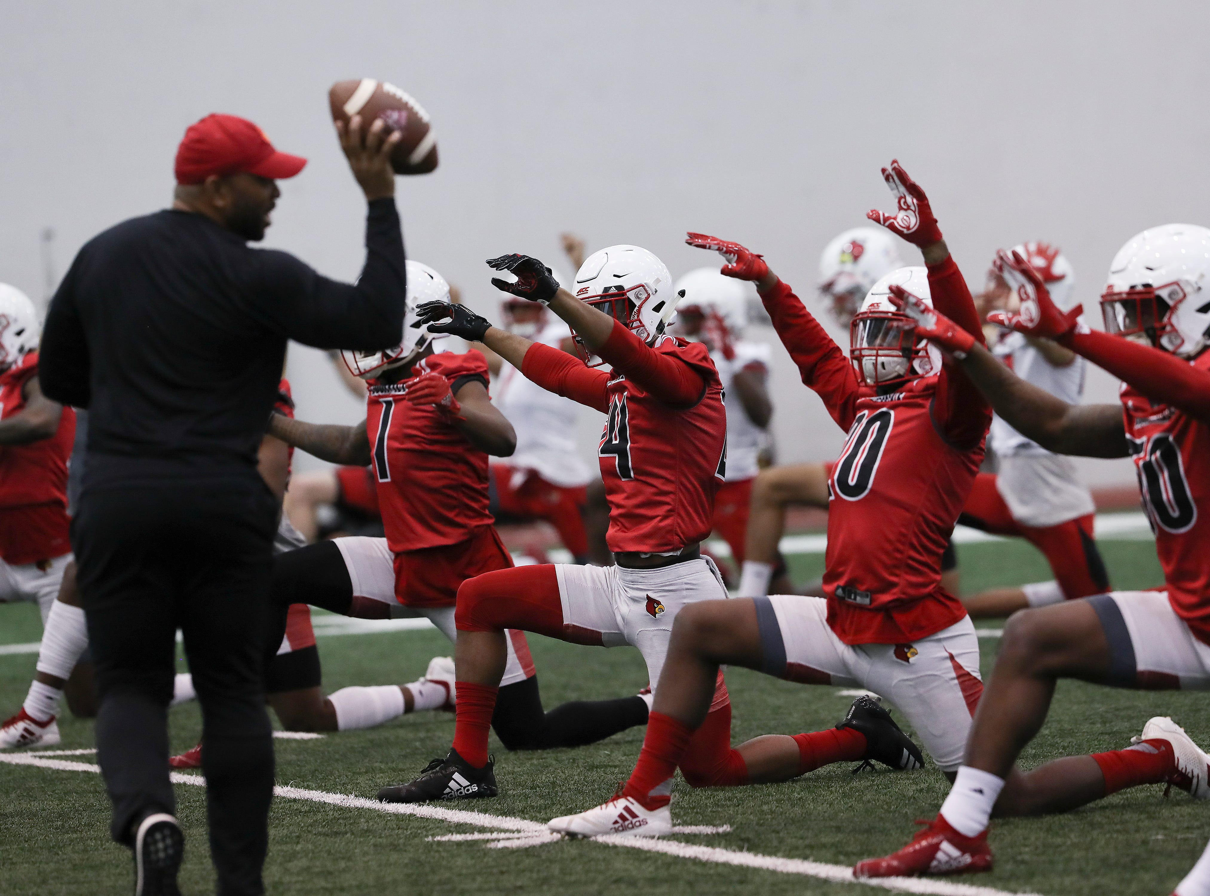 U of L's defensive secondary had a ball tossed to them while stretching during practice at the Trager Center.