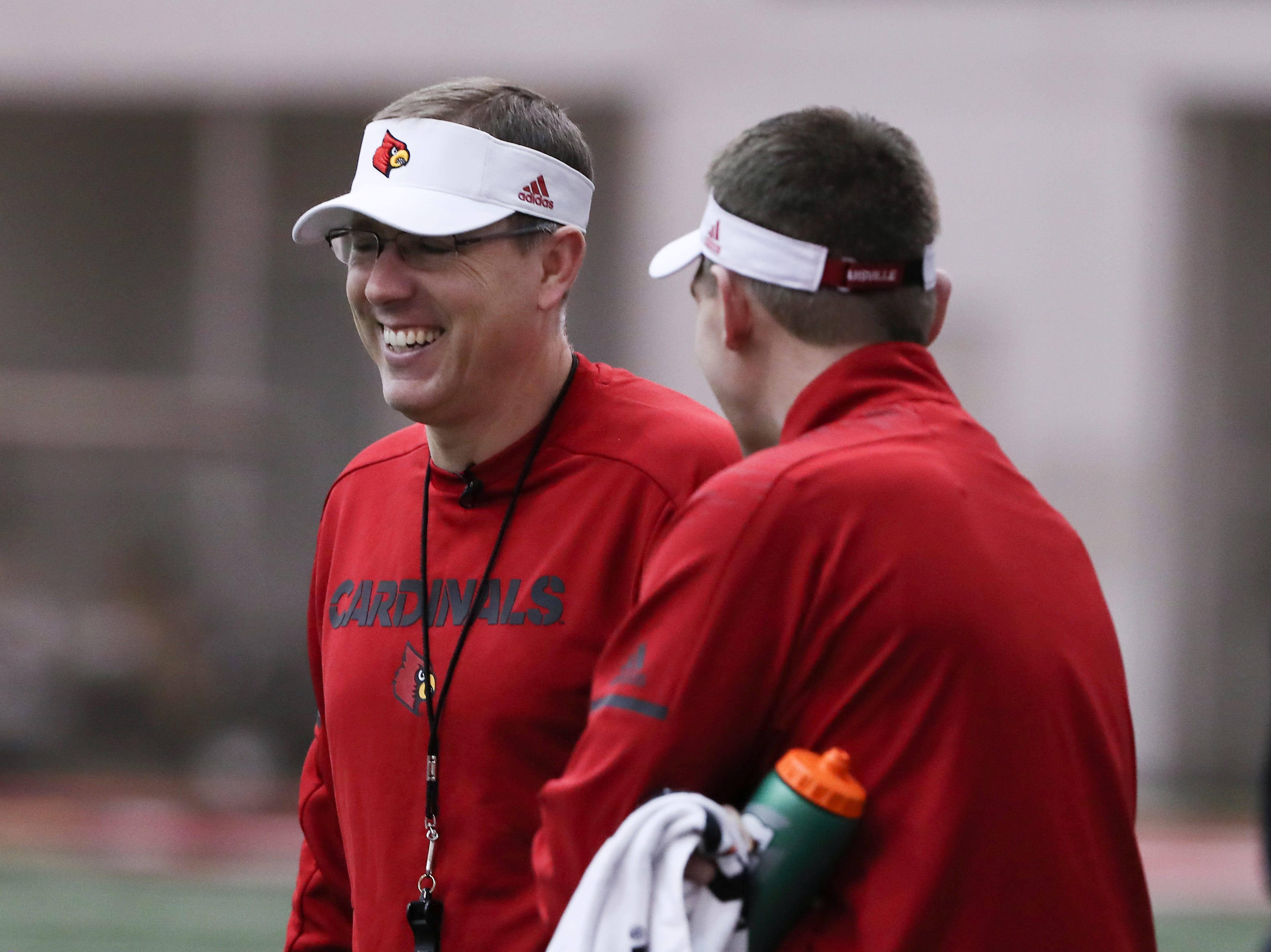 U of L head coach Scott Satterfield, left, shared a laugh with staff during practice at the Trager Center.