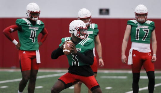 Louisville quarterback Malik Cunningham (3) performs a passing drill as Jawon Pass (4) looks on in the background.