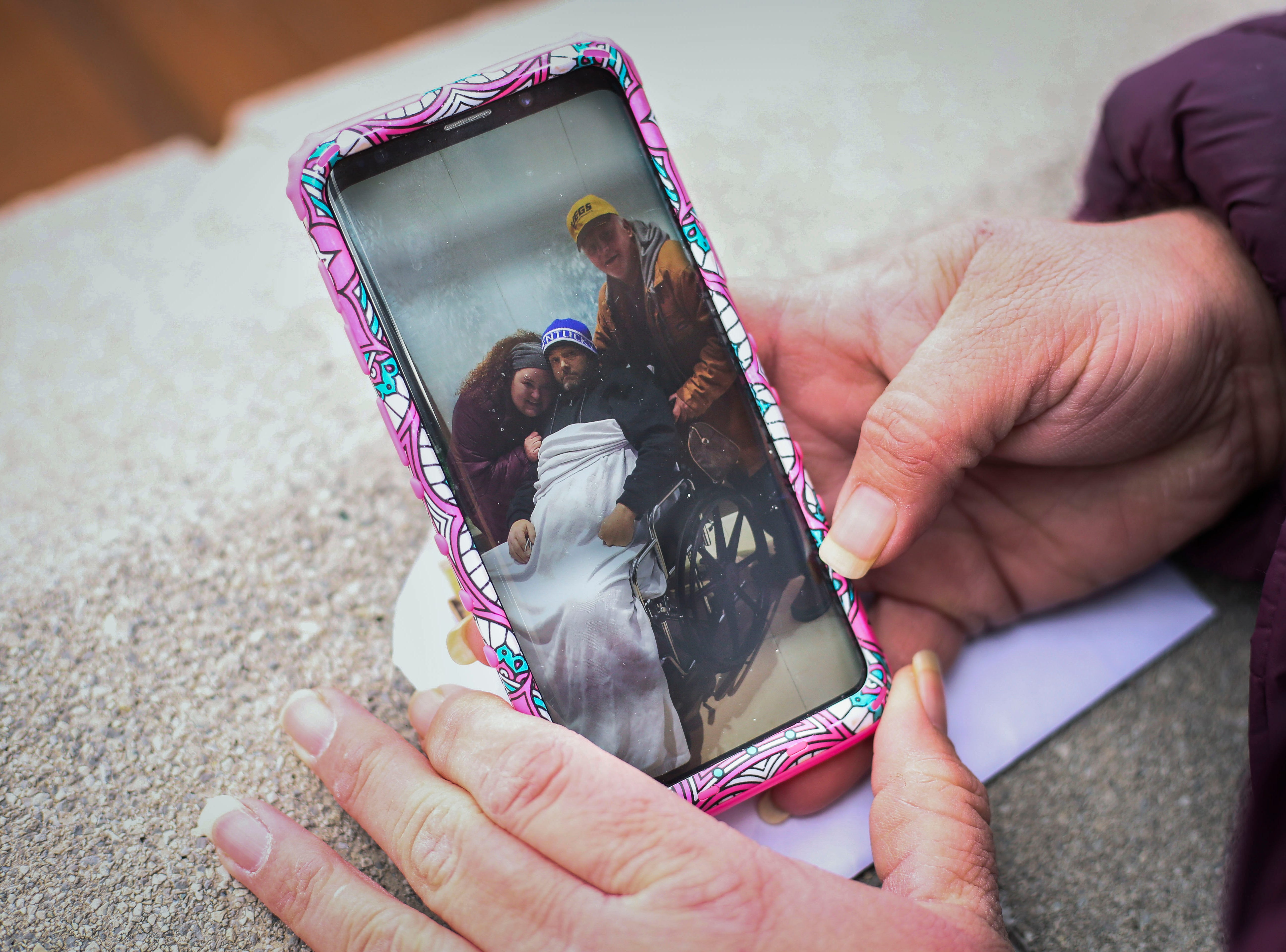 Brandy Stafford shows a photo of herself with her father Tim Ramey, right, and her brother James Ramey from when James was in the hospital in Inez, Kentucky, on Jan. 8, 2019. They lost James to complications due to hepatitis A in November 2018.