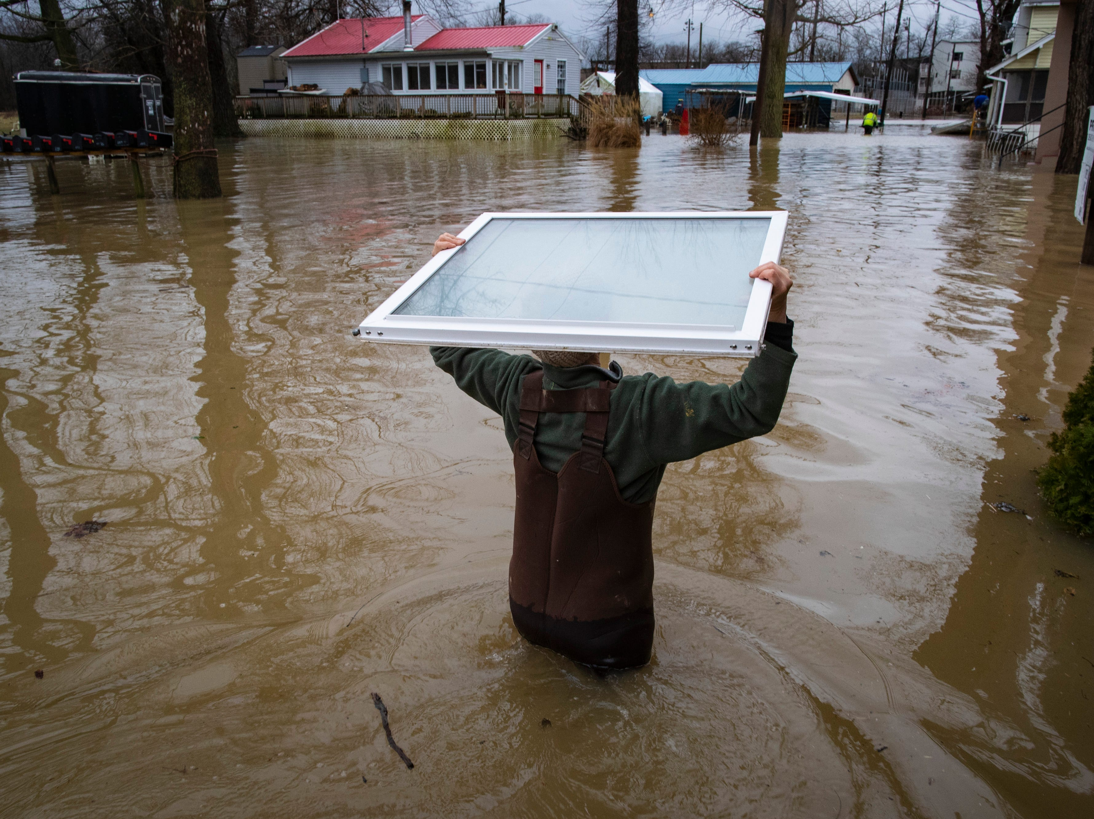 Angelyn Rudd carries her first floor windows up to the second floor of her home off River Road as high waters on the Ohio River rose Tuesday. Feb. 12, 2019