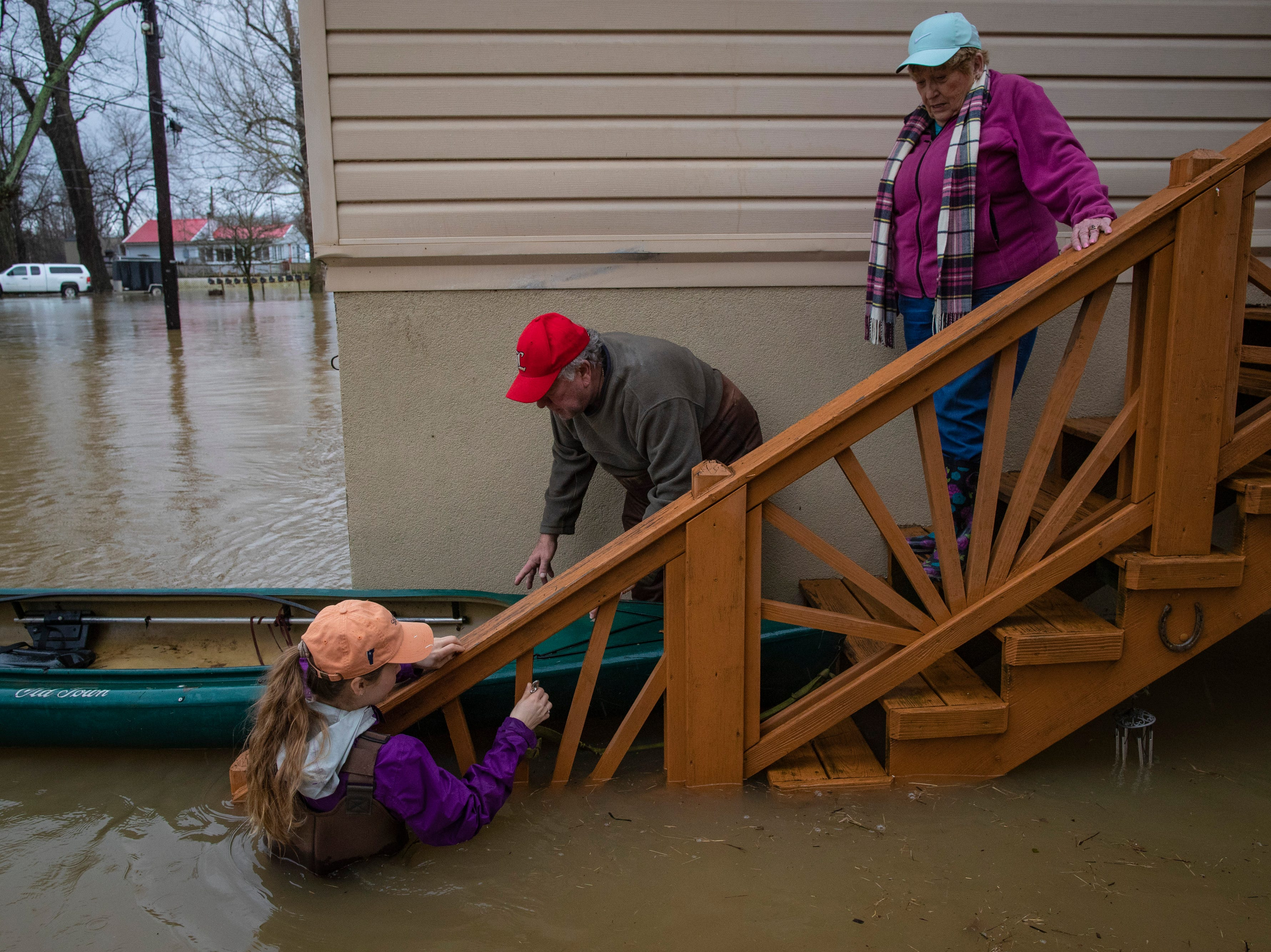 Neighbors help Tony Kerger, 78, center, get his wife Judy Kerger, 77, into a kayak to get her to the couple's vehicle as high waters on the Ohio River rose Tuesday. Feb. 12, 2019