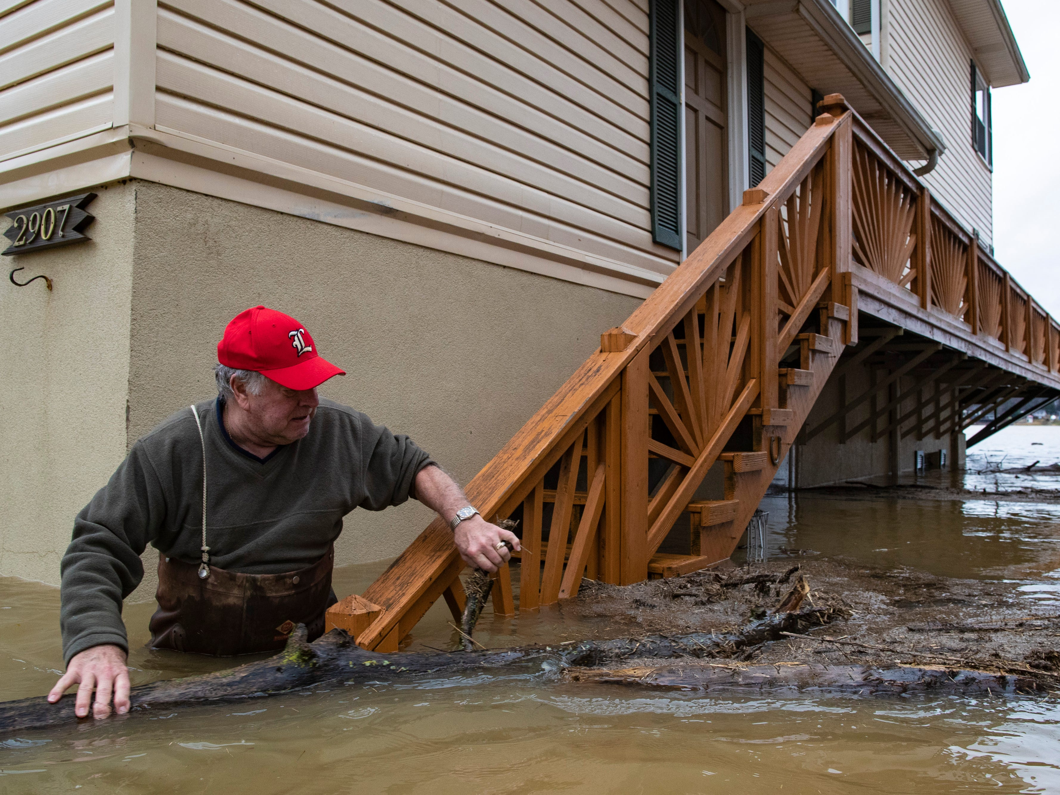 """Tony Kerger, 78, moves debris from the stairway outside his home off River Road as high waters on the Ohio River rose Tuesday. """"We've lived here 44 years,"""" Kerger said. """"Everybod about had their house put back together from last year and now we'll be doing it again."""" Feb. 12, 2019"""