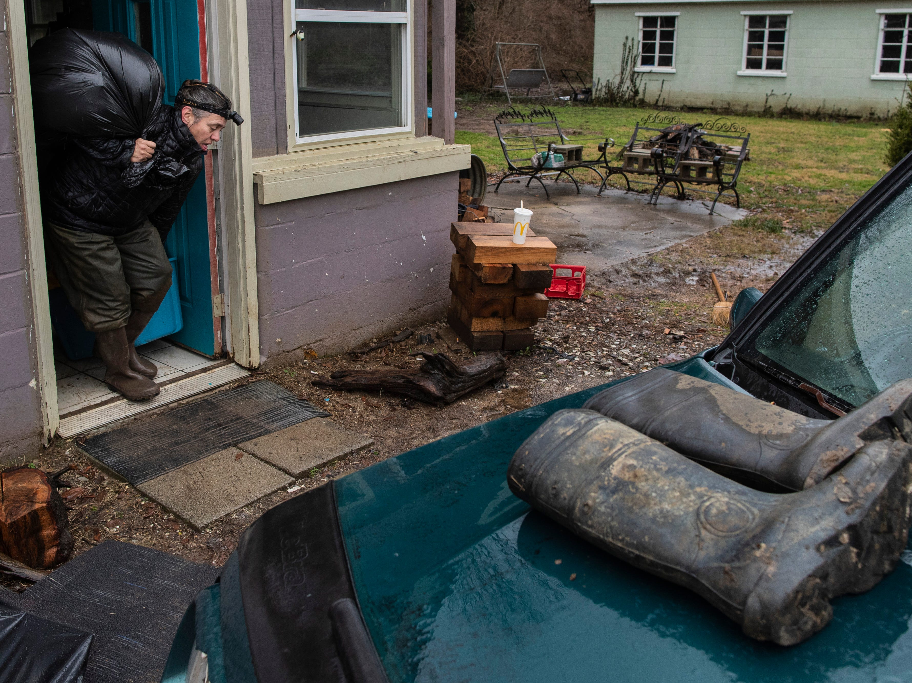Gwennan Thomas helps her friend Chip Jordan load all of his belongings into his vehicle Tuesday to escape the high waters along River Road. Feb. 12, 2019