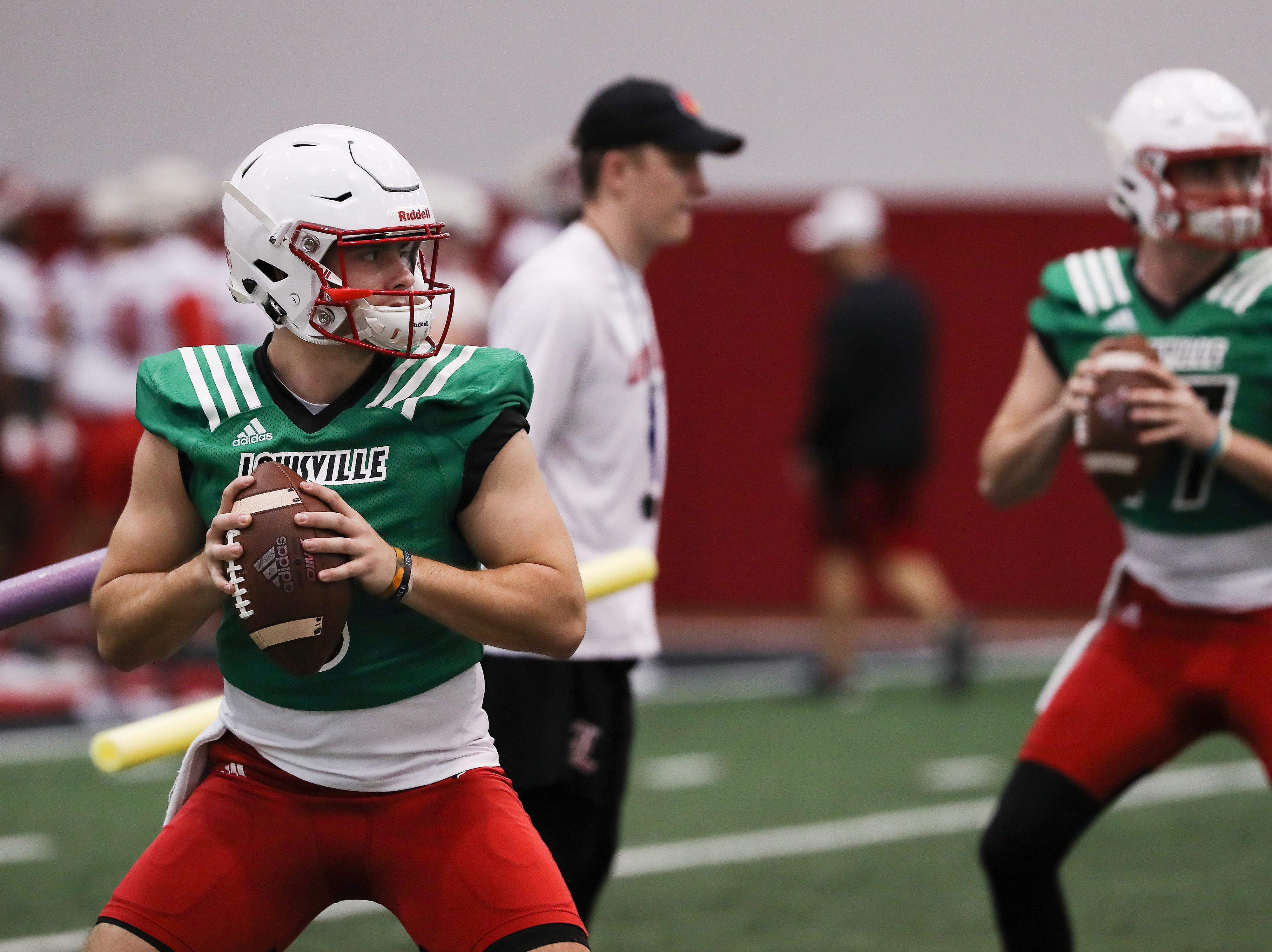 U of L QB's Evan Conley (6), left, and Drew Zaubi (17) perform a pass drill during practice at the Trager Center.