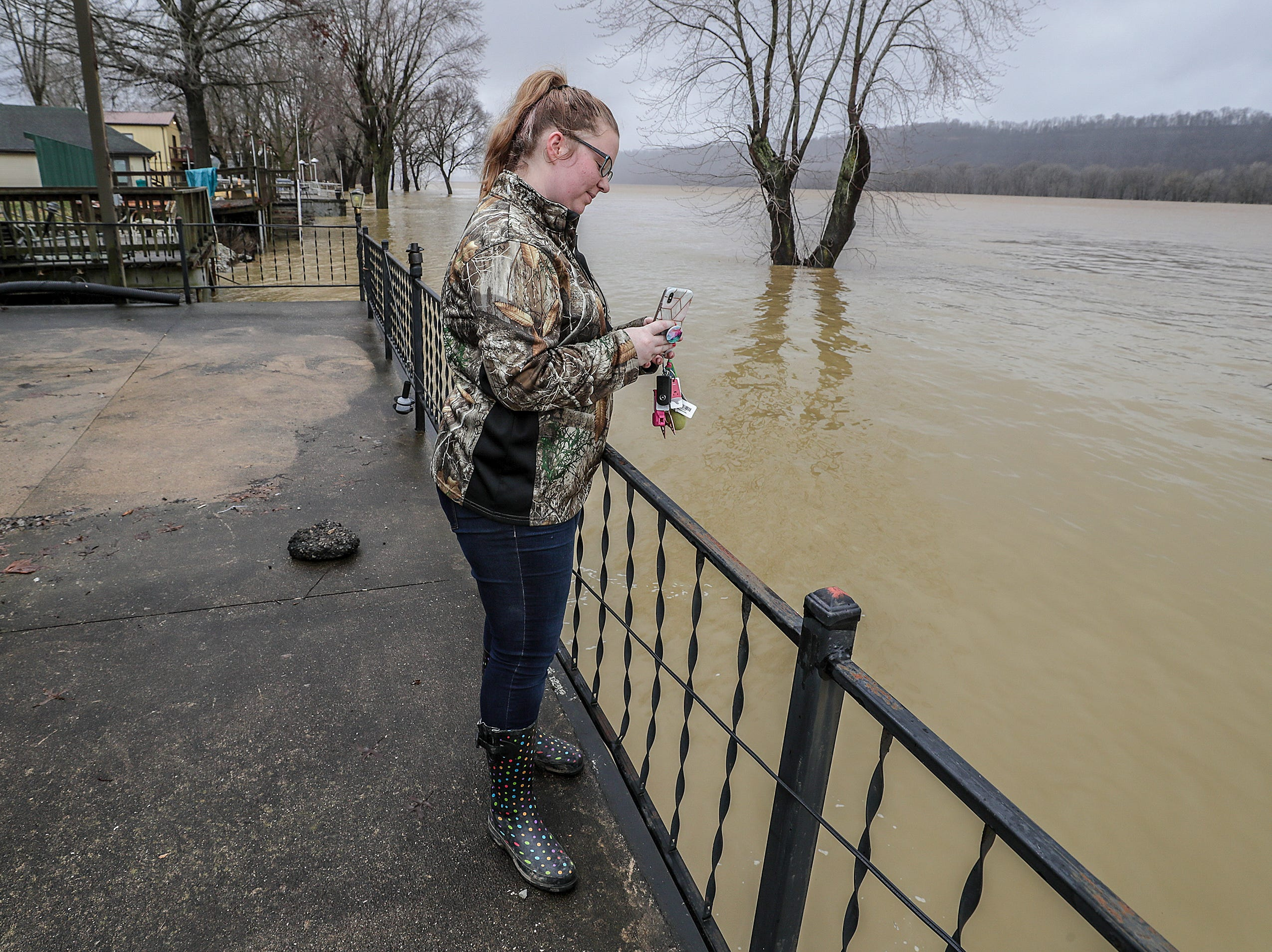 West Point resident Stephanie Hazelwood takes photos of the Ohio River that is forcing many in West Point out of their homes.  There is usually plenty of ground between the river and her back deck.February 12, 2019