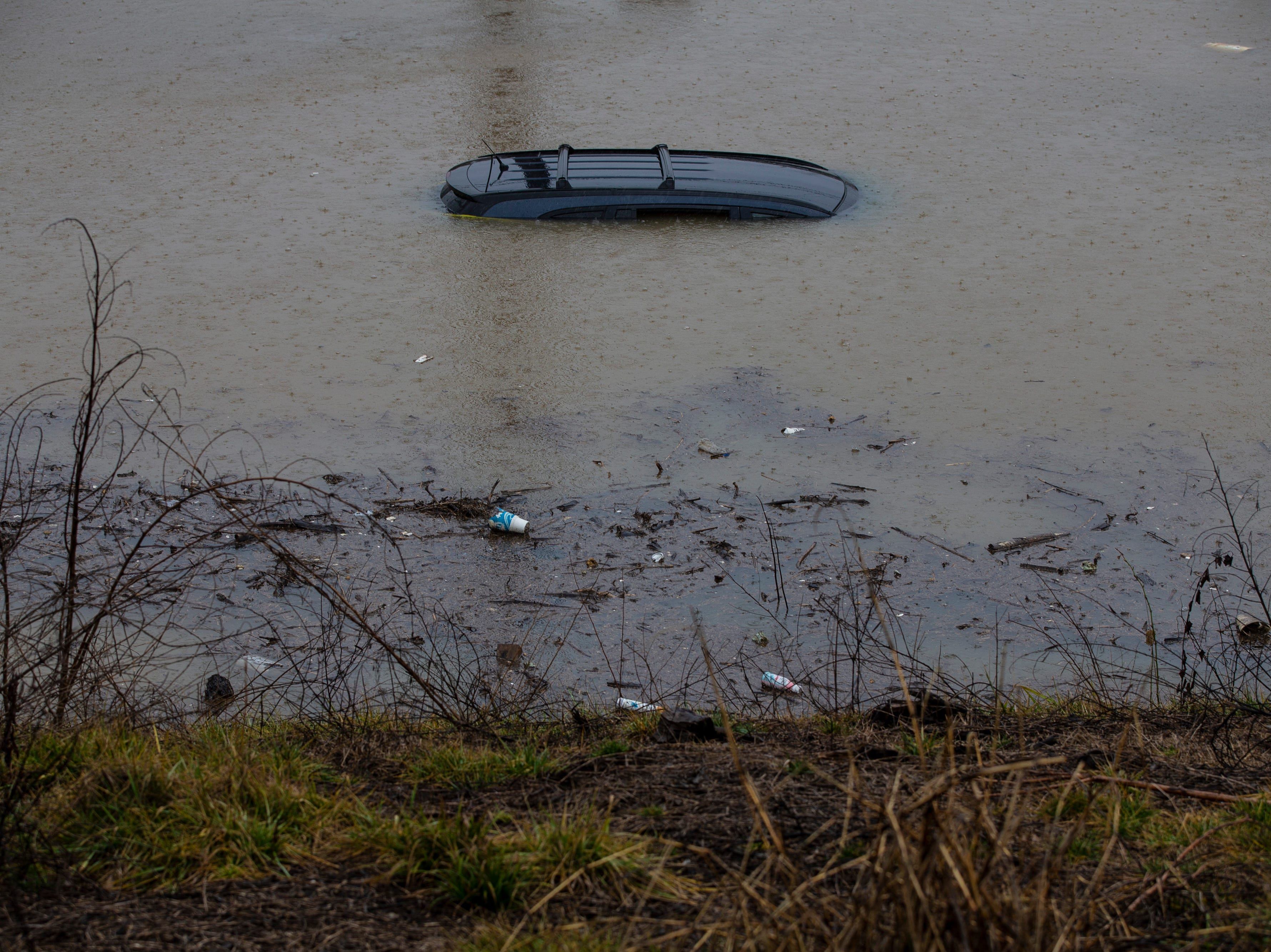 A car sits stuck in high water up to its roof along Frankfort Avenue on Tuesday afternoon in Louisville. Feb. 12, 2019