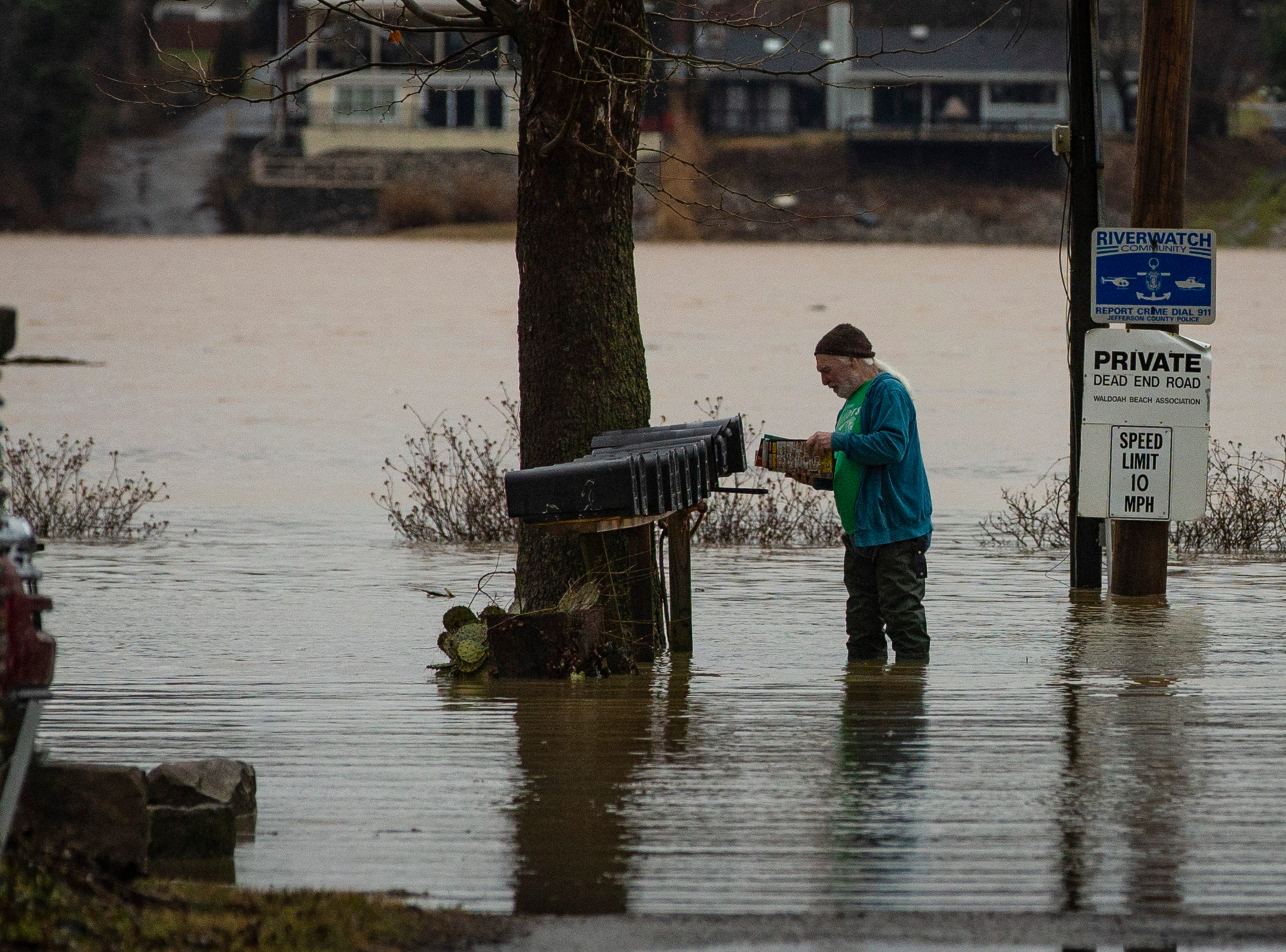 """Tim Lawson checks his mail as as high waters on the Ohio River rose near his home off River Road on Tuesday. This is the second year Lawson has had to endure the high waters. """"I'm a rookie at this,"""" Lawson said. """"Last year it was up over the windows and doors."""" Feb. 12, 2019"""