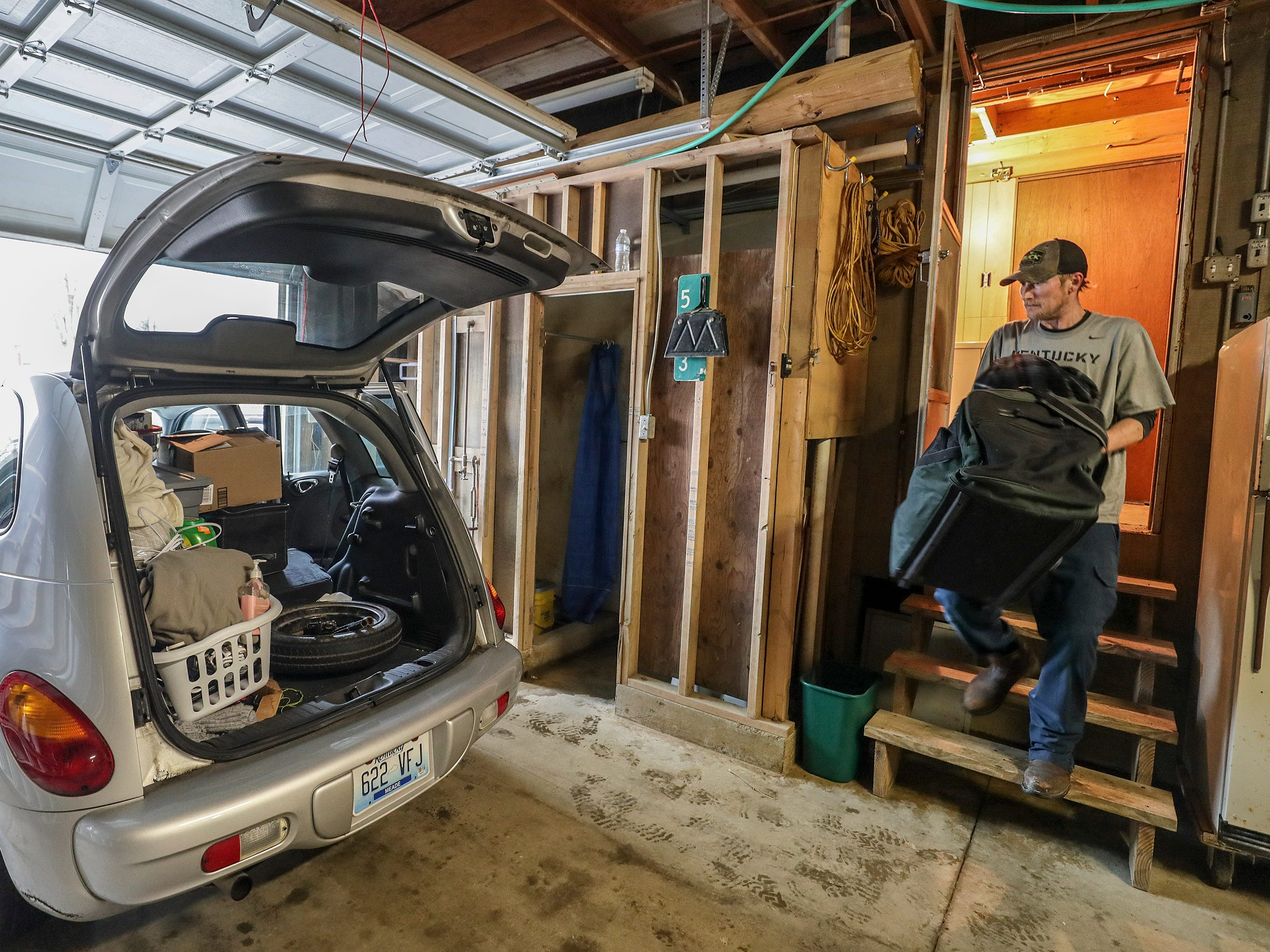 West Point resident Josh Butcher carries items to his car as he and his family begin to move things from the lower level of a home that his family has owned for decades in advance of rising Ohio River water.February 12, 2019
