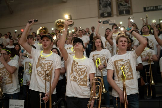 Oakland University student band members hold up their cellphones during 2018 homecoming weekend.