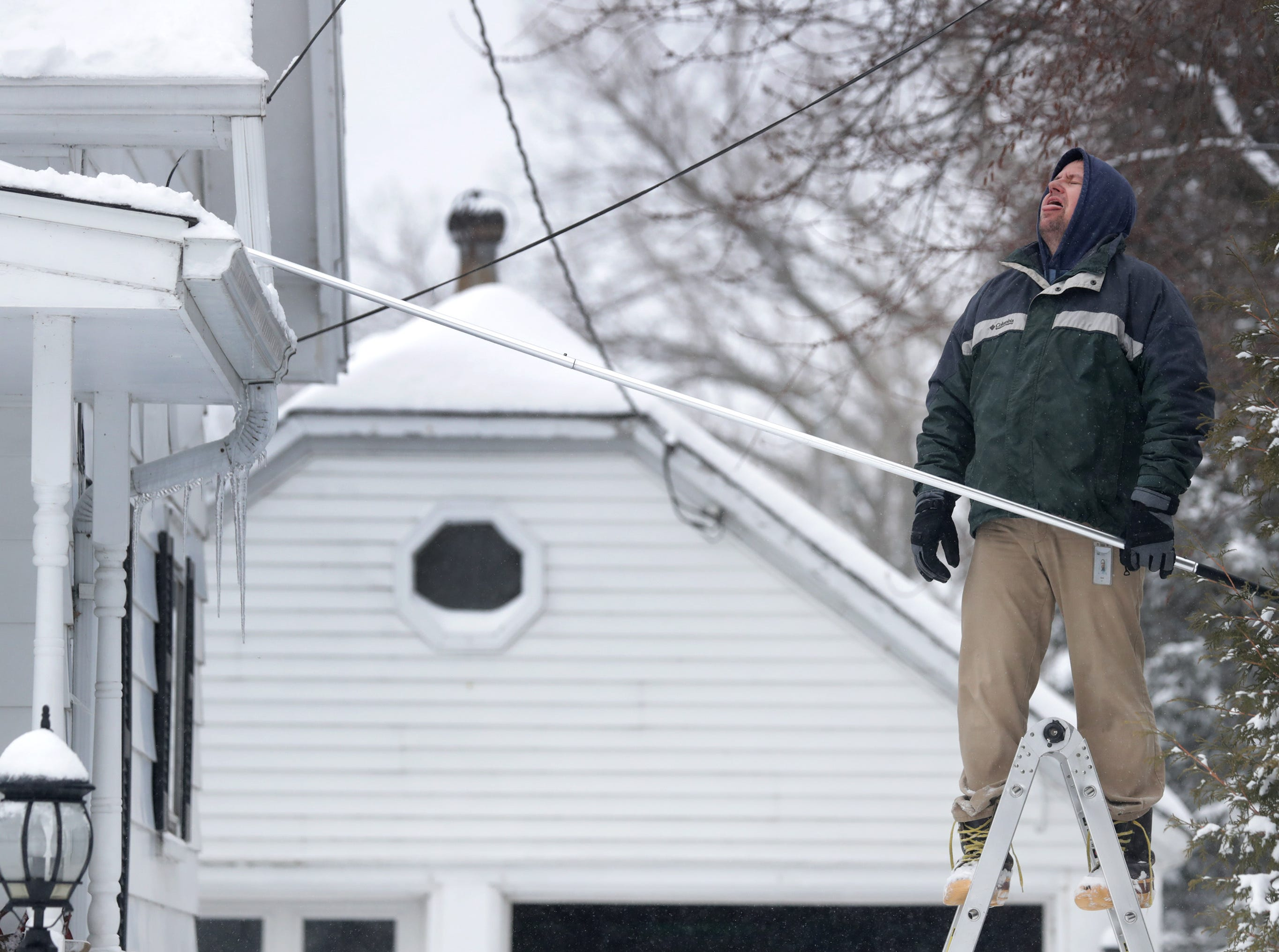 Jason Griffith takes a break from clearing snow off of the roof of his house and to catches a snowflake on his tongue on Tuesday, February 12, 2019, in Little Chute, Wis. The latest snow storm to move through the state dropped several inches of snow overnight, 6 to 12 inches are expected by Tuesday evening.