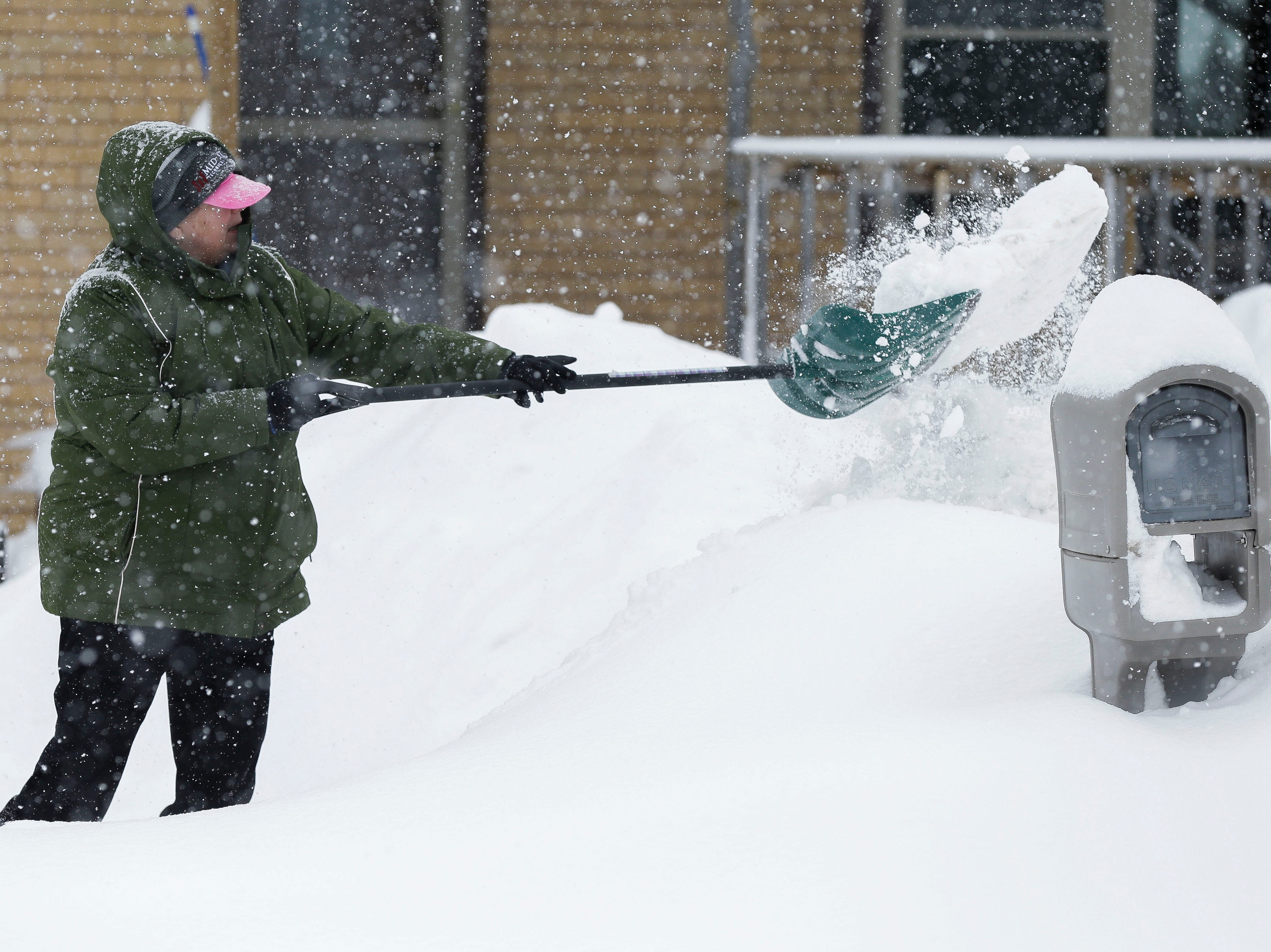 Diana Kohn shovels snow from her driveway on Tuesday, February 12, 2019, in Stevens Point, Wis. A winter storm is expected to drop 8-11 inches of snow in central Wisconsin before clearing Tuesday night.