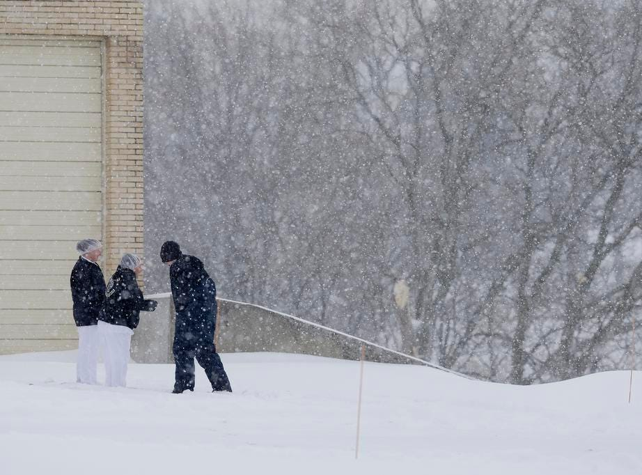 Employees of Cedar Crest Ice Cream take a break to check out the snow Tuesday, February 12, 2019, in Manitowoc, Wis. The latest winter storm to hit Wisconsin is expected to bring 6-12 inches by the end of Tuesday.