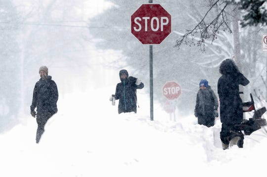 Lars Smith, Kelly Smith and Tully Smith, 9, walk home on Tuesday, February 12, 2019, in Stevens Point, Wis. A winter storm is expected to drop 8-11 inches of snow in central Wisconsin before clearing Tuesday night.
