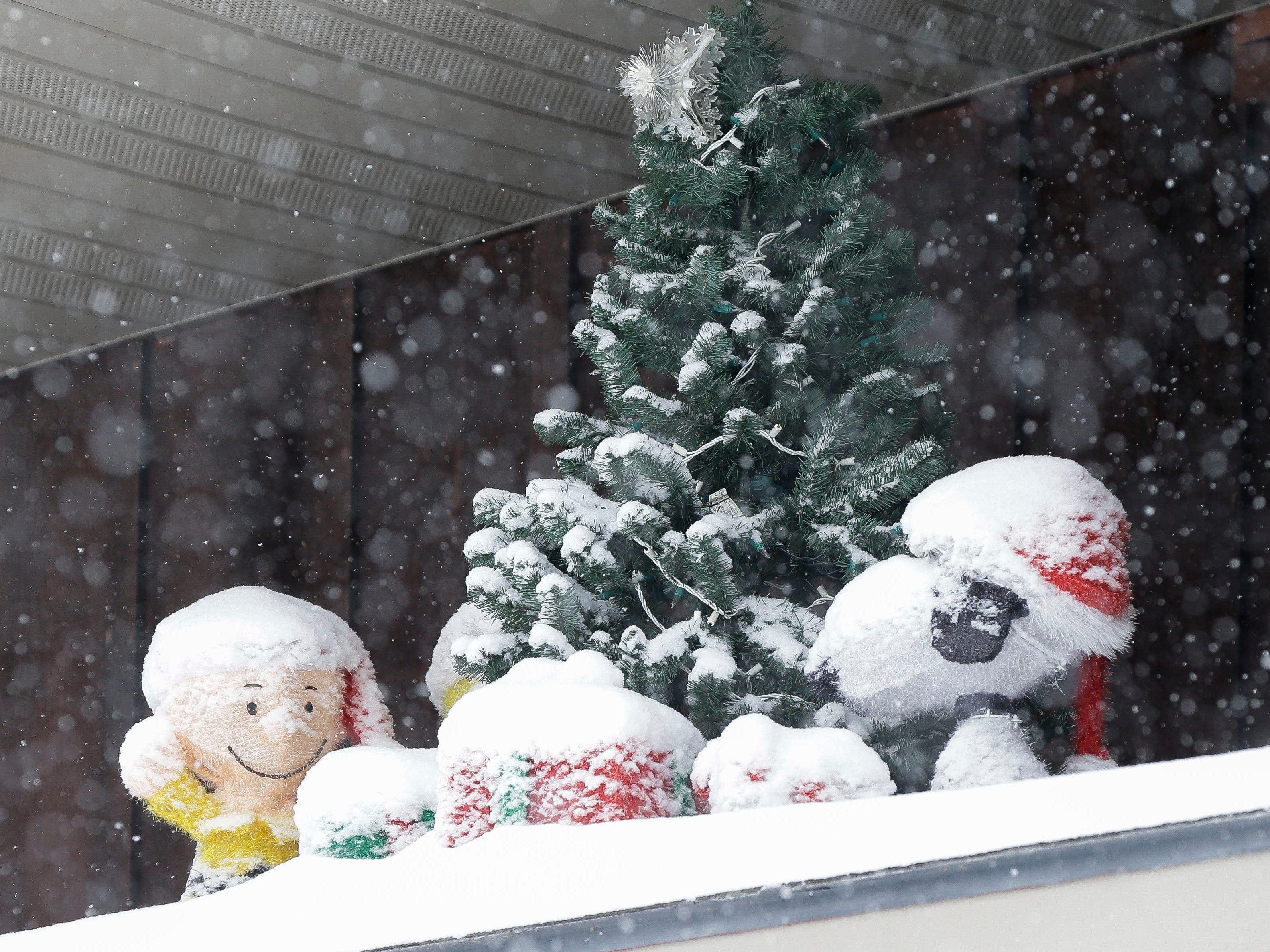 A Peanuts-themed display is covered by snow on Tuesday, February 12, 2019, in Stevens Point, Wis. A winter storm is expected to drop 8-11 inches of snow in central Wisconsin before clearing Tuesday night.