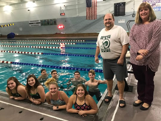 Head coach Chad Reynolds with assistant Melissa Parish and the eight Madison swimmers who have qualified for this week's district meet at Bowling Green.