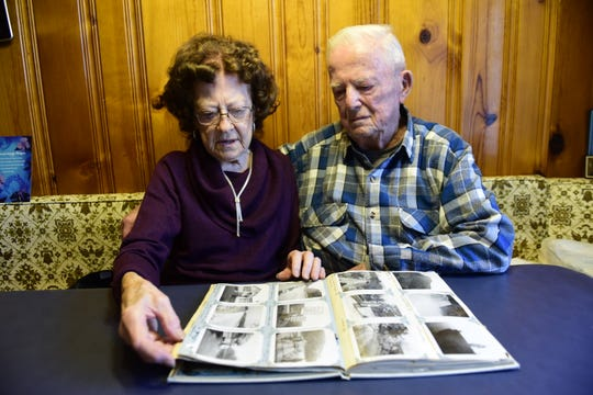 Freda and Linas Bishop look over photos from their honeymoon 70 years ago.