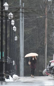 A woman uses an umbrella to stay dry Tuesday morning as the rain falls during her walk up Walnut Street.