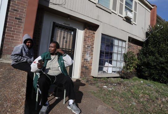 """Tyrone Davis shares headphones with his son Devaughn, 10, outside of their rented Fox Hollow Townhome, where owners and management spent the afternoon in Shelby County's environmental court addressing the blight and trash removal issues at the Fox Meadows community on Tuesday, Feb. 12, 2019. """"It's pitiful. This is where we live, and it is messy,"""" said Davis who has rented a home there for the last year. """"It gets so rough, that, I've got three boys and put I put them to work out here."""""""