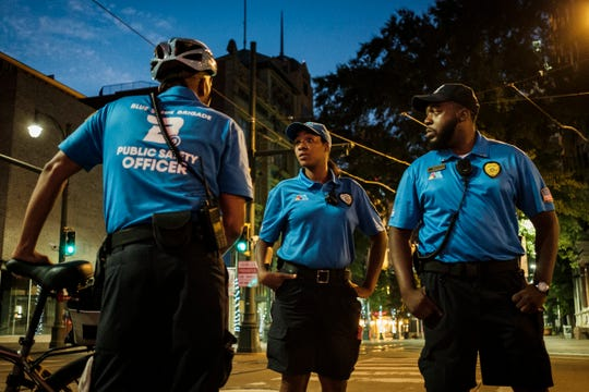 Blue Suede Brigade members from left: Kcbena Cash, Tamala Johnson and Nathaniel Lewis talk after breaking up an altercation between two homeless men on North Main St. in Downtown Memphis.