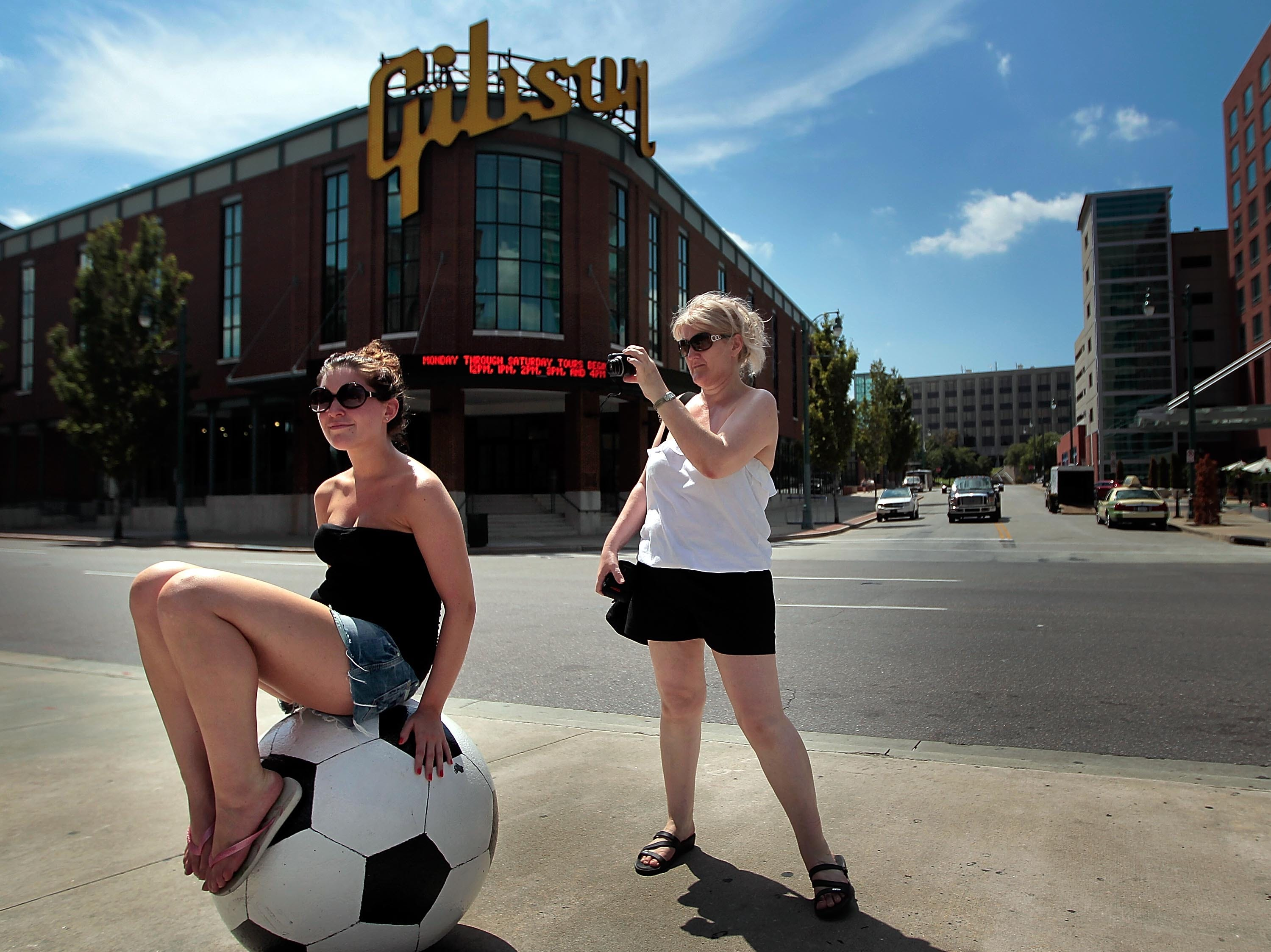 Aug. 6, 2012 - Tourist Sharon Mottershead of Britan takes pictures of her daughter Natalie Mottershead in front of the FedEx Forum after visiting the Gibson Guitar factory to pick up guitar strings for her son.