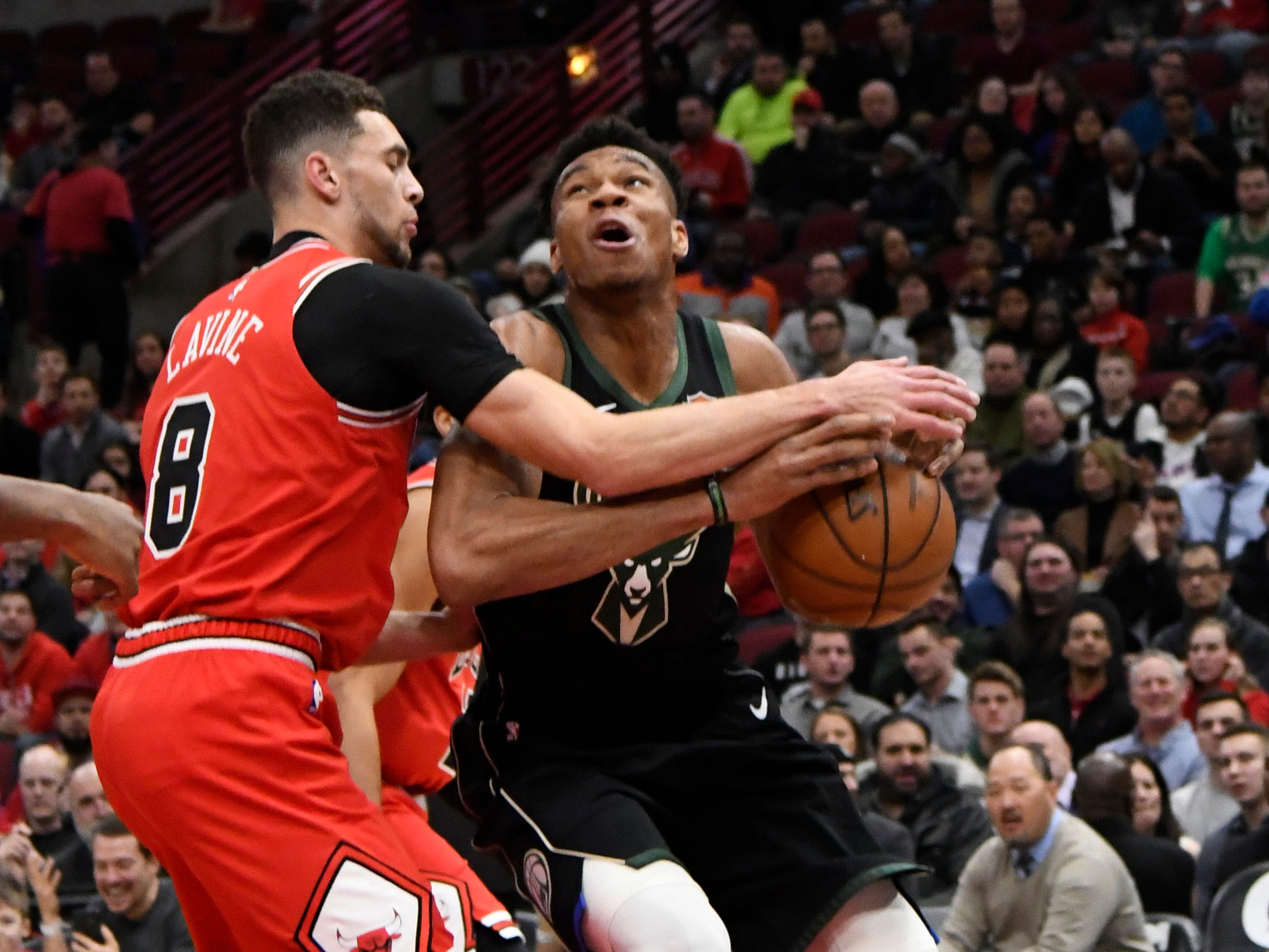 Bucks forward Giannnis Antetokounmpo has the ball knocked out of his hands by Bulls guard Zach LaVine as he works under the basket during the first half Monday.