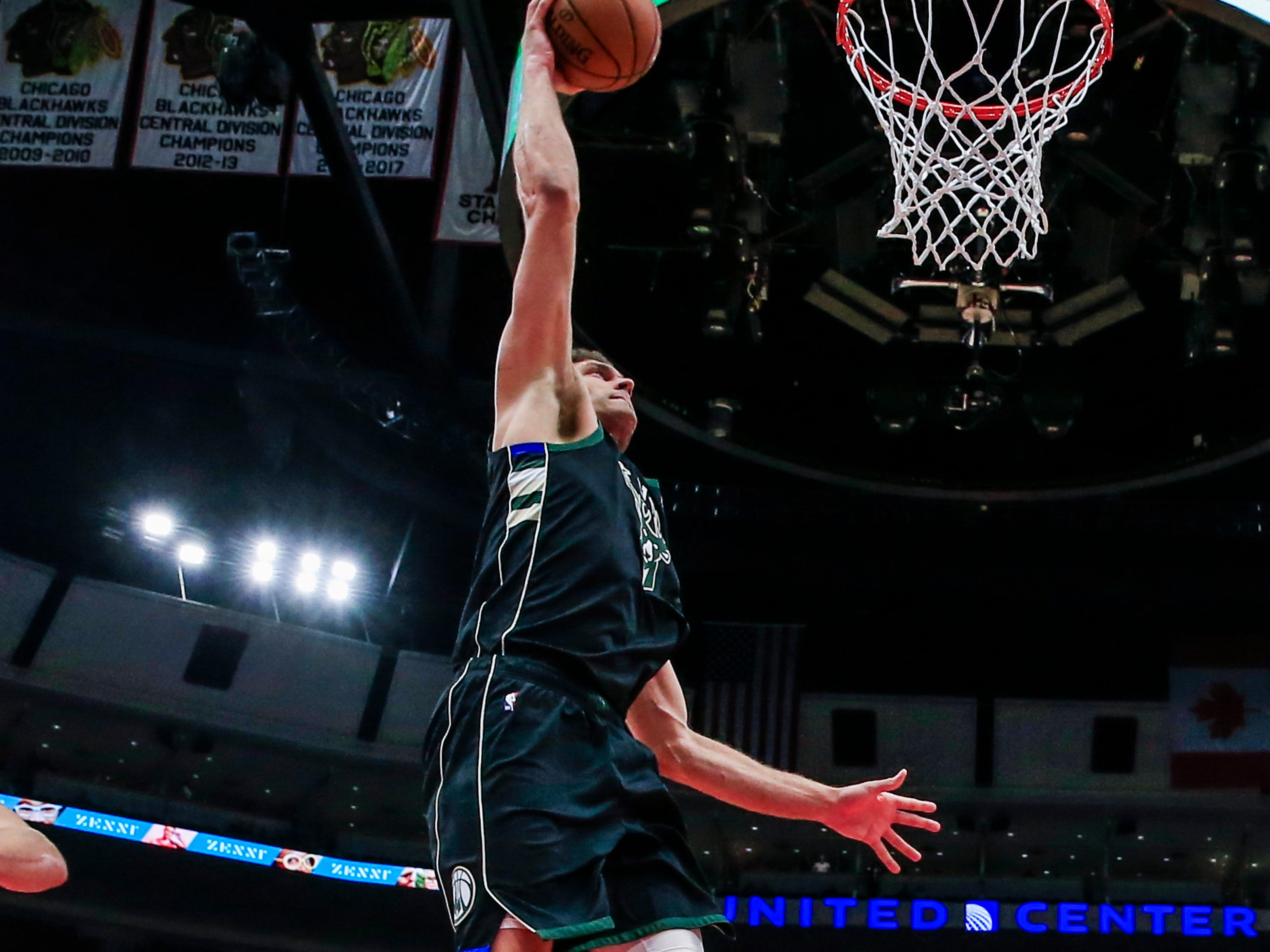 Bucks center Brook Lopez is set to power home a dunk as Lauri Markkanen (left) and Robin Lopez of the Bulls look on during the second half Monday.
