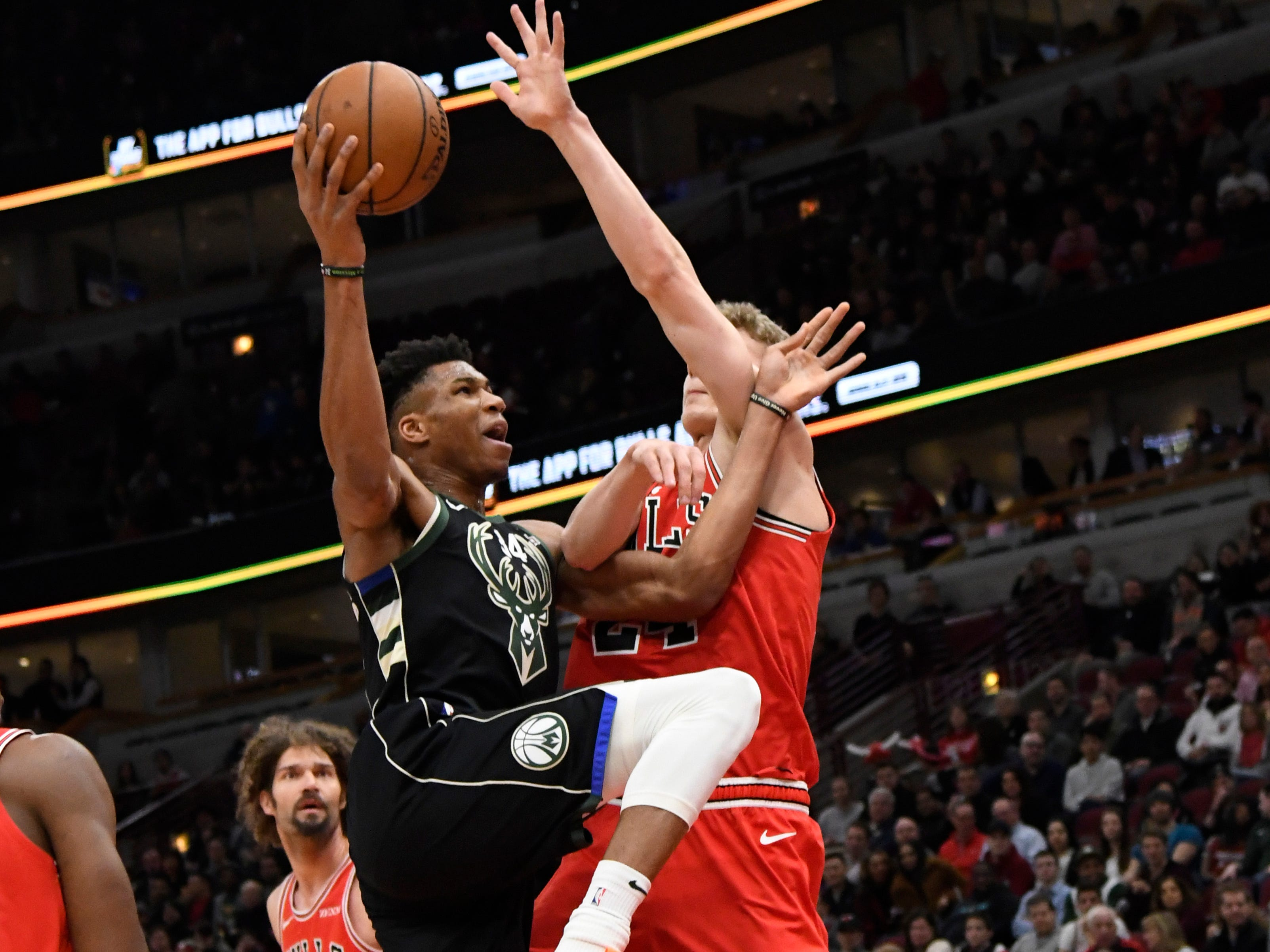 Bucks forward Giannis Antetokounmpo drives to the basket as Bulls forward Lauri Markkanen defends him during the first half Monday.