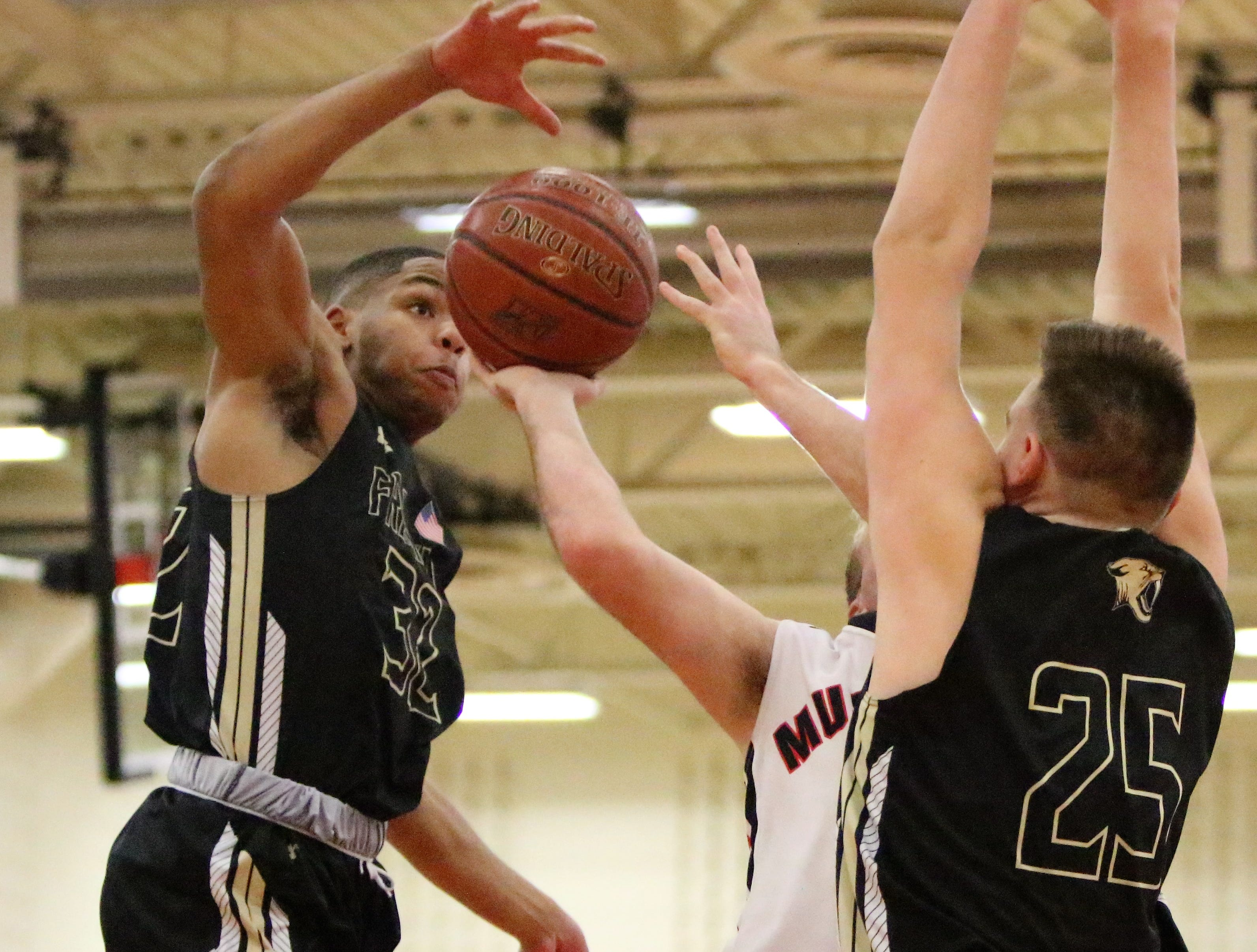 Franklin guard Ron Wilson (left) goes up to block a shot against Muskego on Feb. 11, 2019.