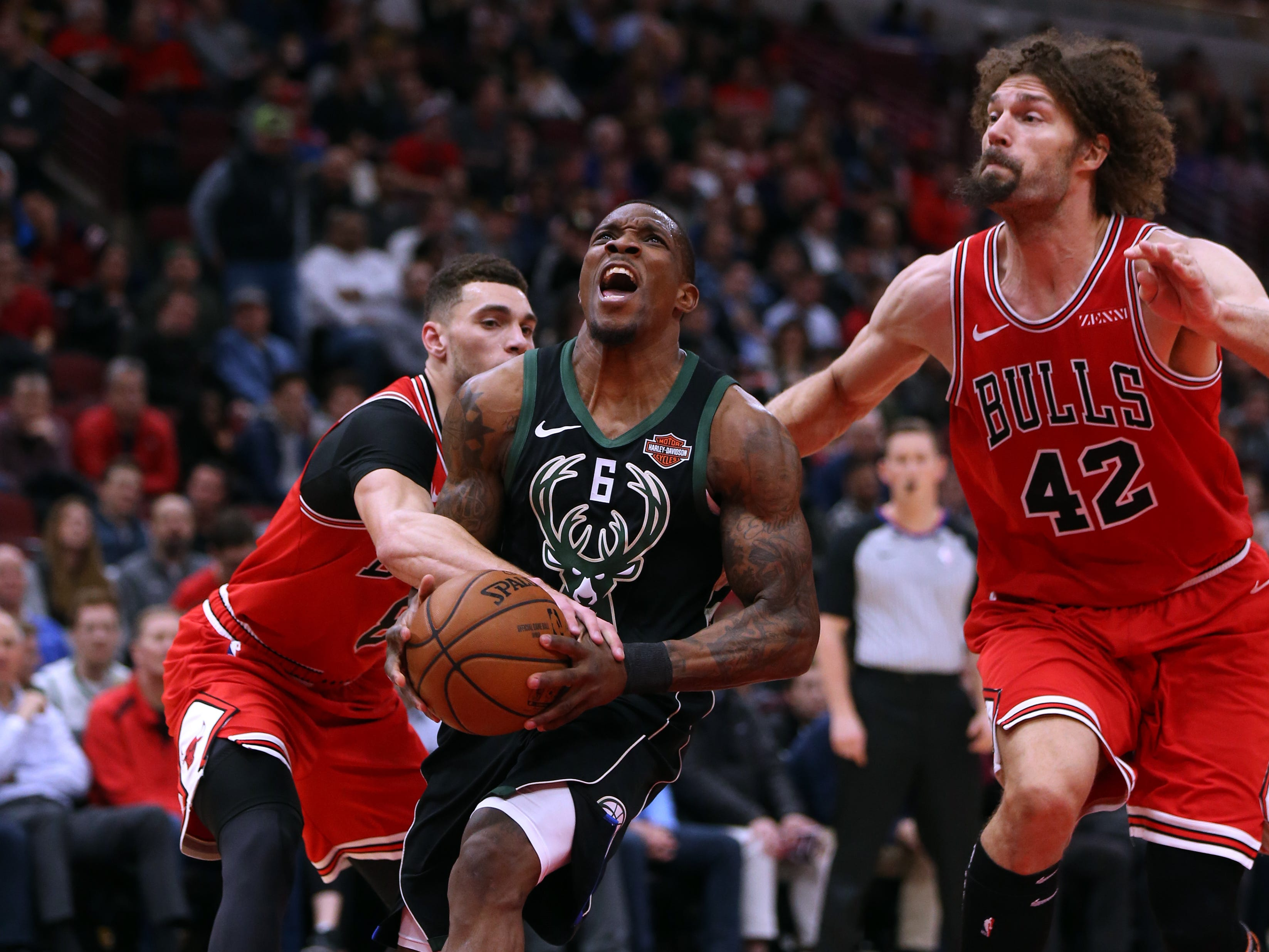 Bucks guard Eric Bledsoe is fouled by Bulls guard Zach LaVine (left) as he drives to the basket with Chicago center Robin Lopez closing in during the first half Monday.