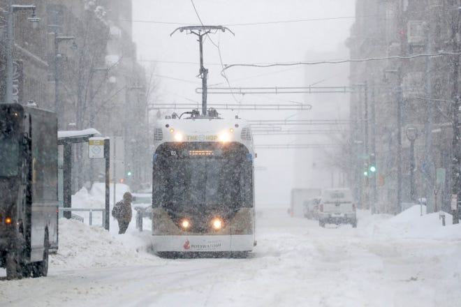 The Hop streetcar makes its way  through the snow down North Milwaukee Street.