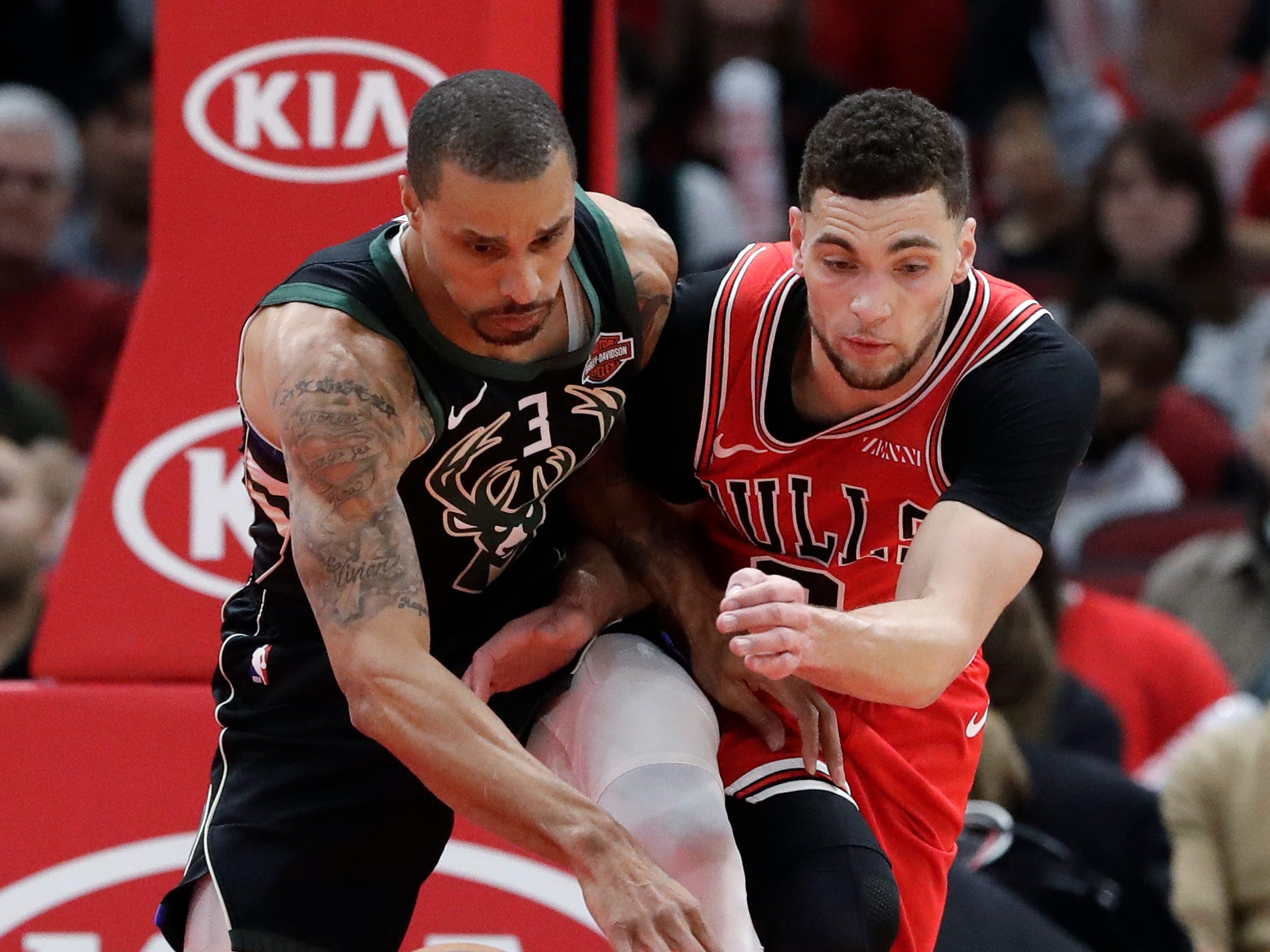 Bucks guard George Hill battles for a loose ball against Bulls guard Zach LaVine during the first half Monday.